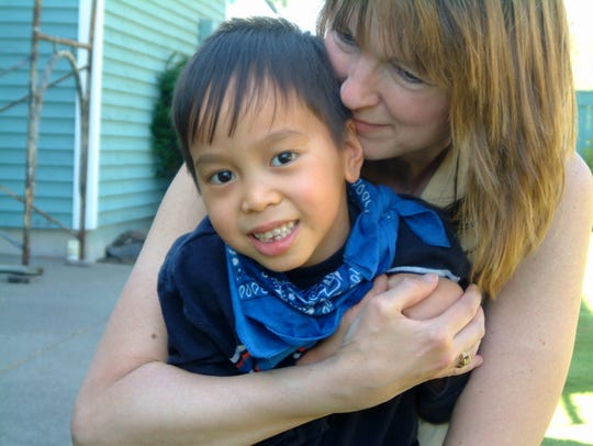Jaxon Abalahin is with his mom Paula before his death in 2008 of subacute sclerosing panencephalitis, a complication of measles. Jaxon had measles at seven months old as an orphan in the the Philippines before Paula and Oscar Abalahin adopted him. The couple founded Jaxon's Cure in 2007 to raise awareness of the importance of immunizations.