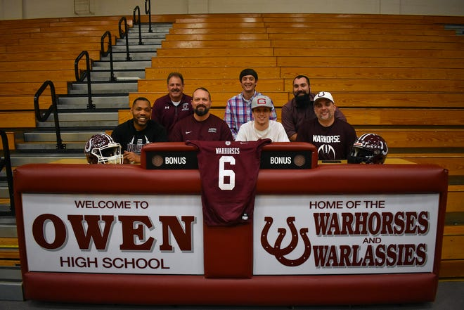 Surrounded by his coaches and father Rob Meyers (right), Owen senior Audun Meyers signs with Guilford College, where he plans to continue his football career.