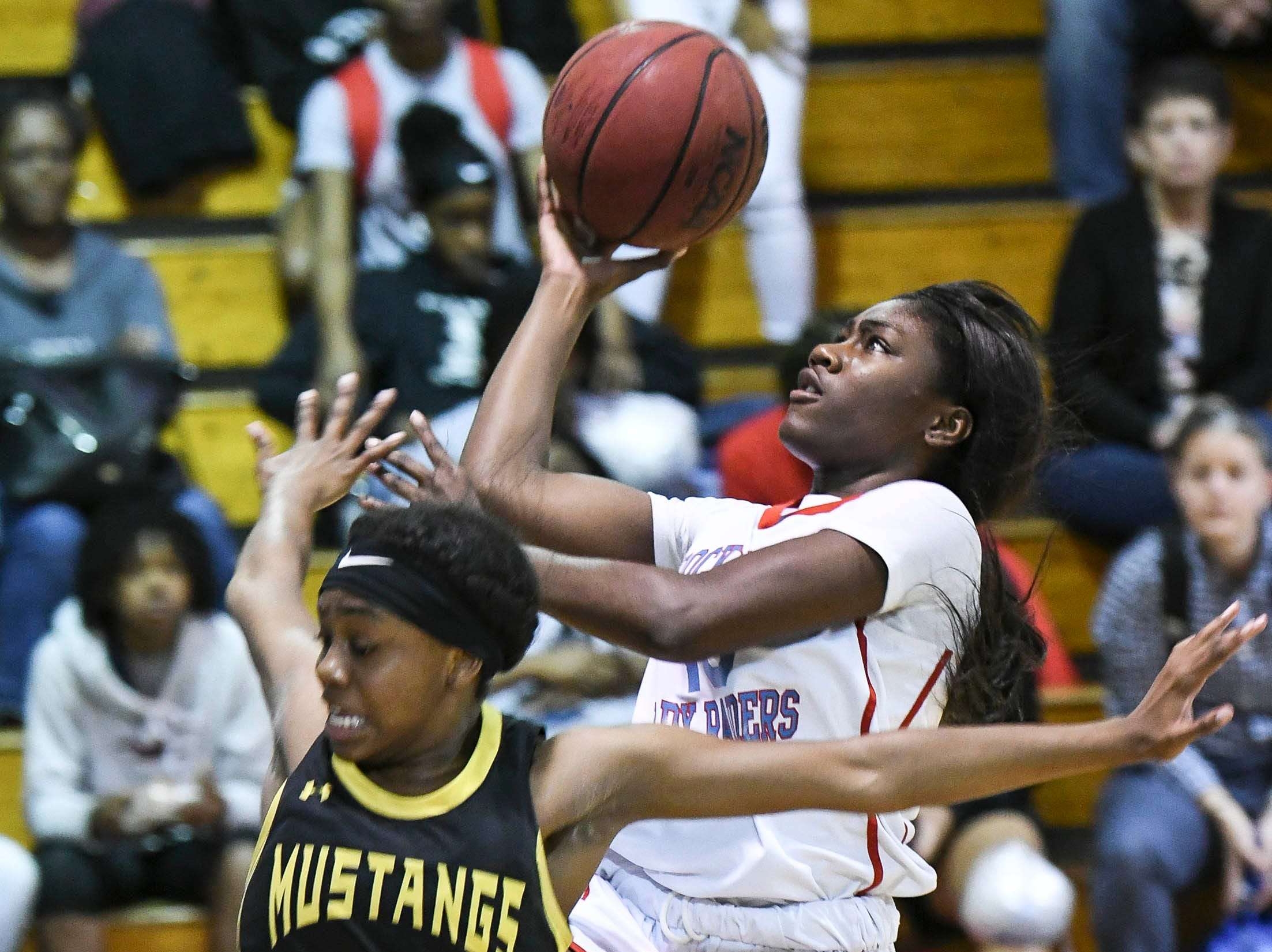Zykeena Arthur of Rockledge shoots over the guard of Merritt Island's Essynce Hall during Thursday's District 14-6A basketball tournament semifinal at Rockledge High School.