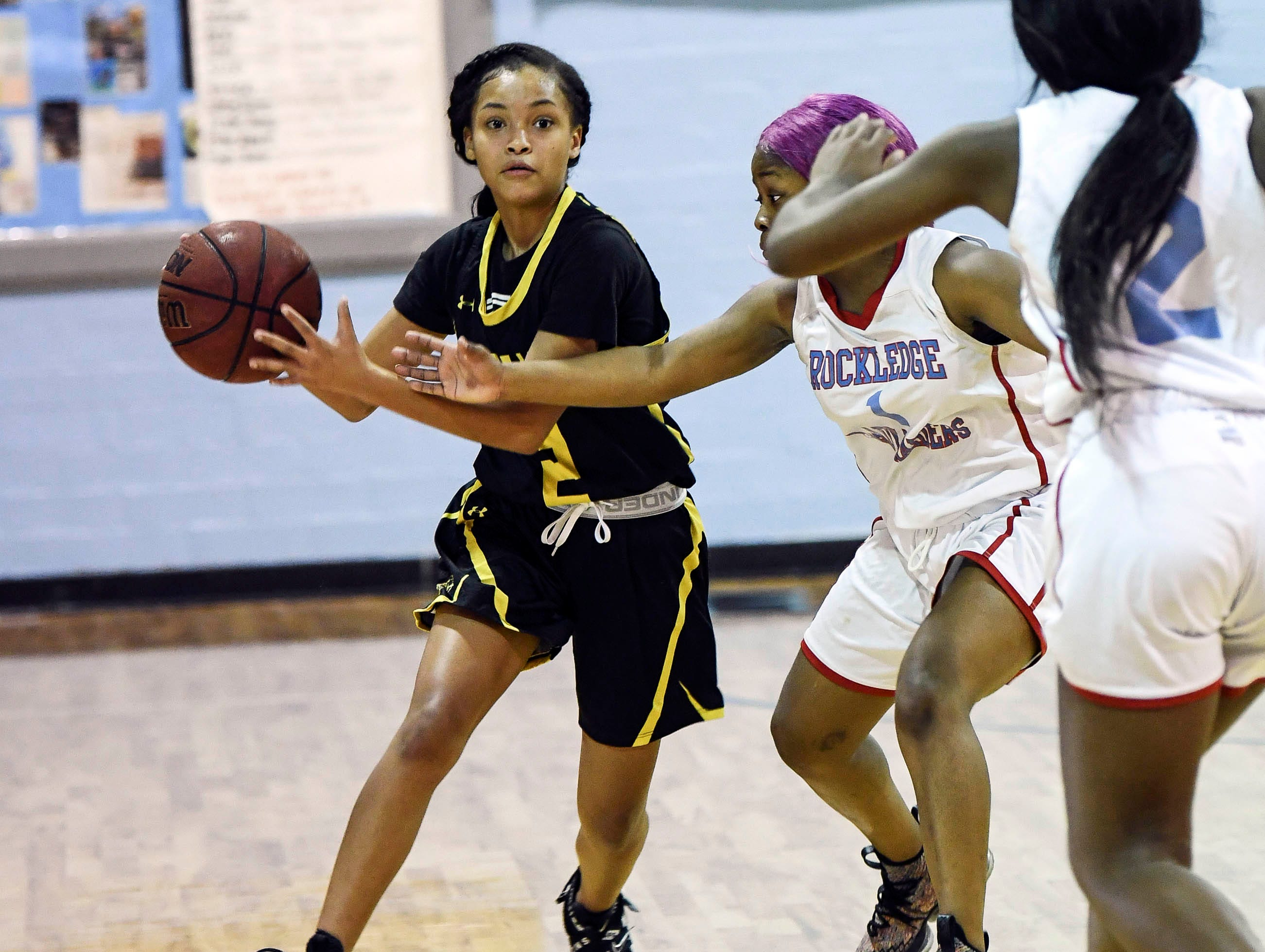 Shakira Fernandez of Merritt tries to drive through  a Rockledge double team District 14-6A basketball tournament at Rockledge High School.