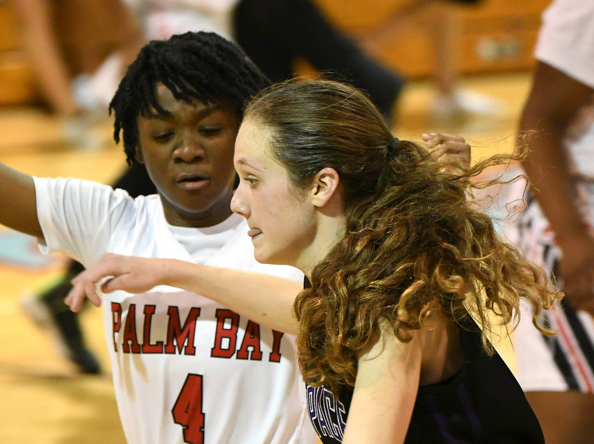 Ashley Cathon of Space Coast is guarded by Palm Bay's Mykaila Burgher during Thursday's District 14-6A basketball tournament semifinal at Rockledge High School.