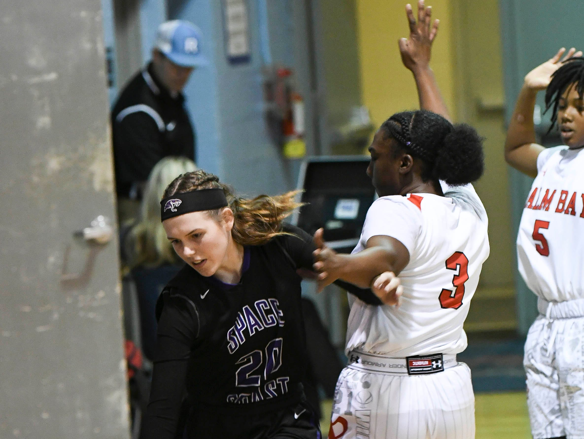 Lily Prelde of Space Coast drives the baseline around the guard of Palm Bay's Ari Jordan during Thursday's District 14-6A basketball tournament at Rockledge High School.