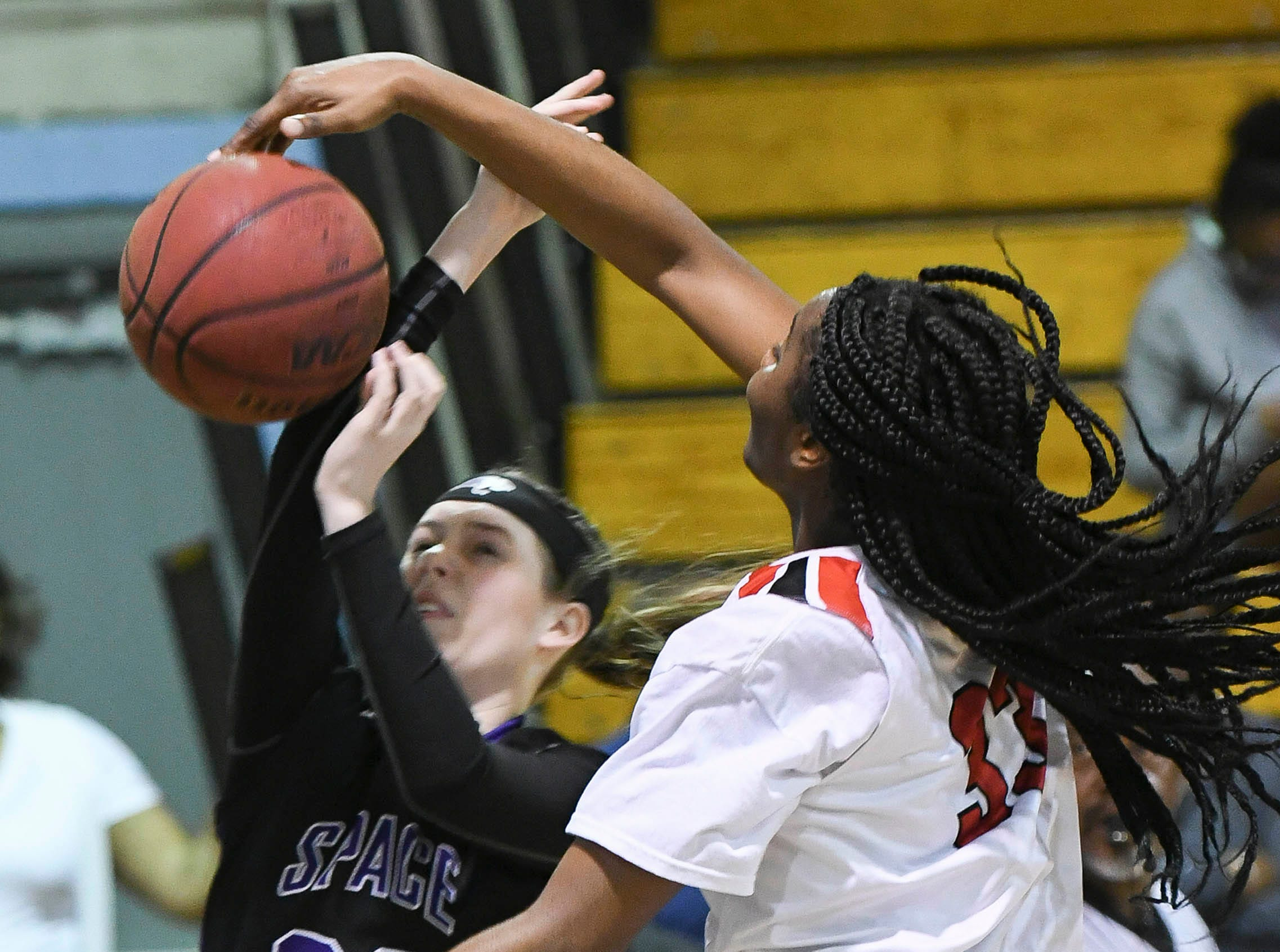 Lily Prelde of Space Coast has her shot blocked b Emani Burks of Palm Bay during Thursday's District 14-6A basketball tournament semifinal at Rockledge High School.