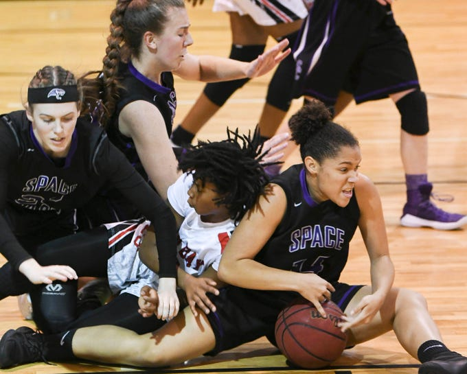 Space Coast and Palm Bay players battle for loose ball during Thursday's District 14-6A basketball tournament semifinal at Rockledge High School.
