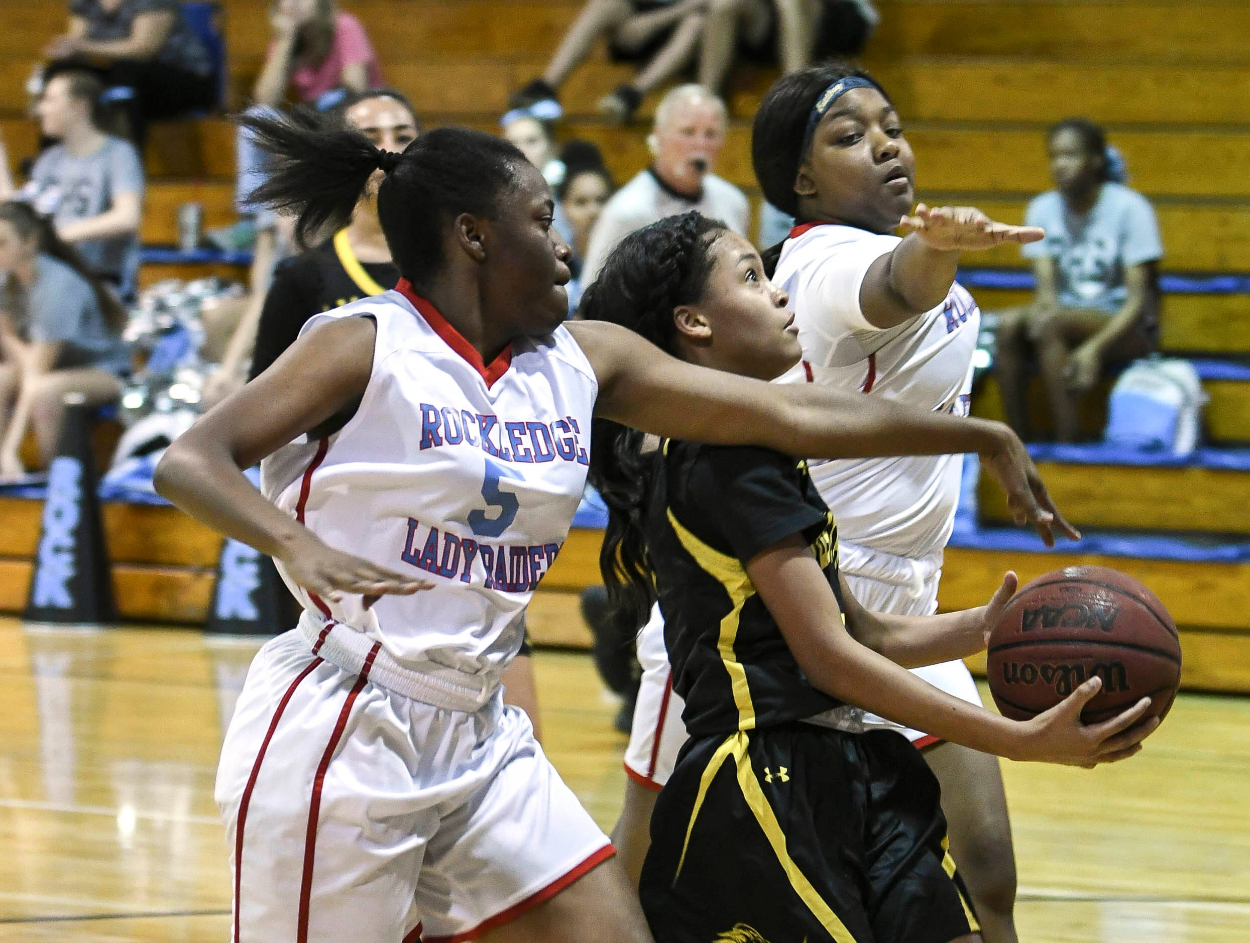 Crystal Brown and Zarea Baker of Rockledge try to prevent Shakira Fernandez of Merritt Island from scoring during Thursday's District 14-6A basketball tournament at Rockledge High School.