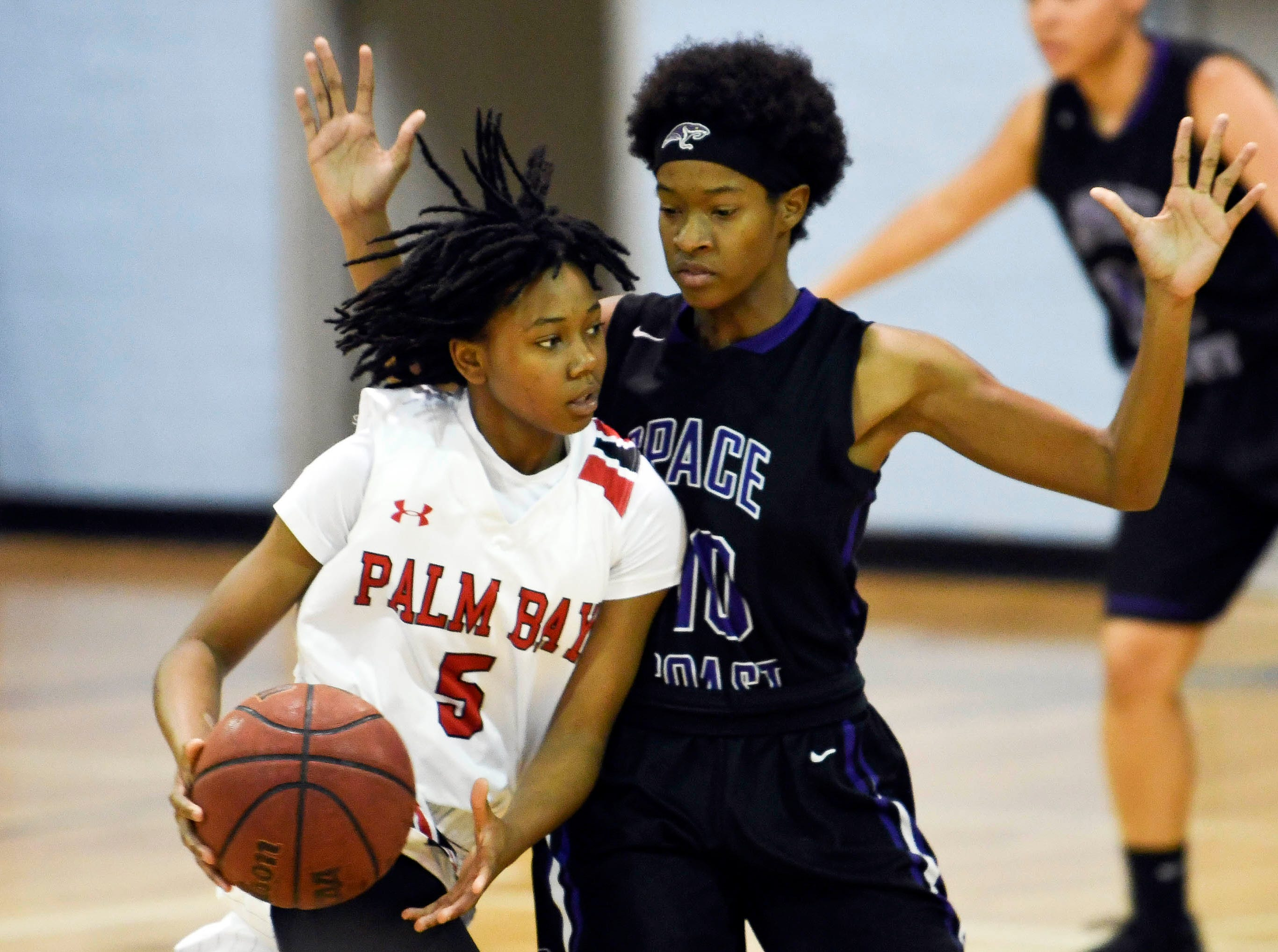 Amaya Bozeman of Palm Bay is guarded by Syniah Johnson of Space Coast during Thursday's District 14-6A basketball tournament semifinal at Rockledge High School.