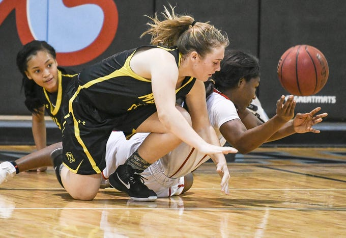 Merritt Island and Rockledge players chase a loose ball during the District 14-6A basketball tournament semifinal at Rockledge High School.