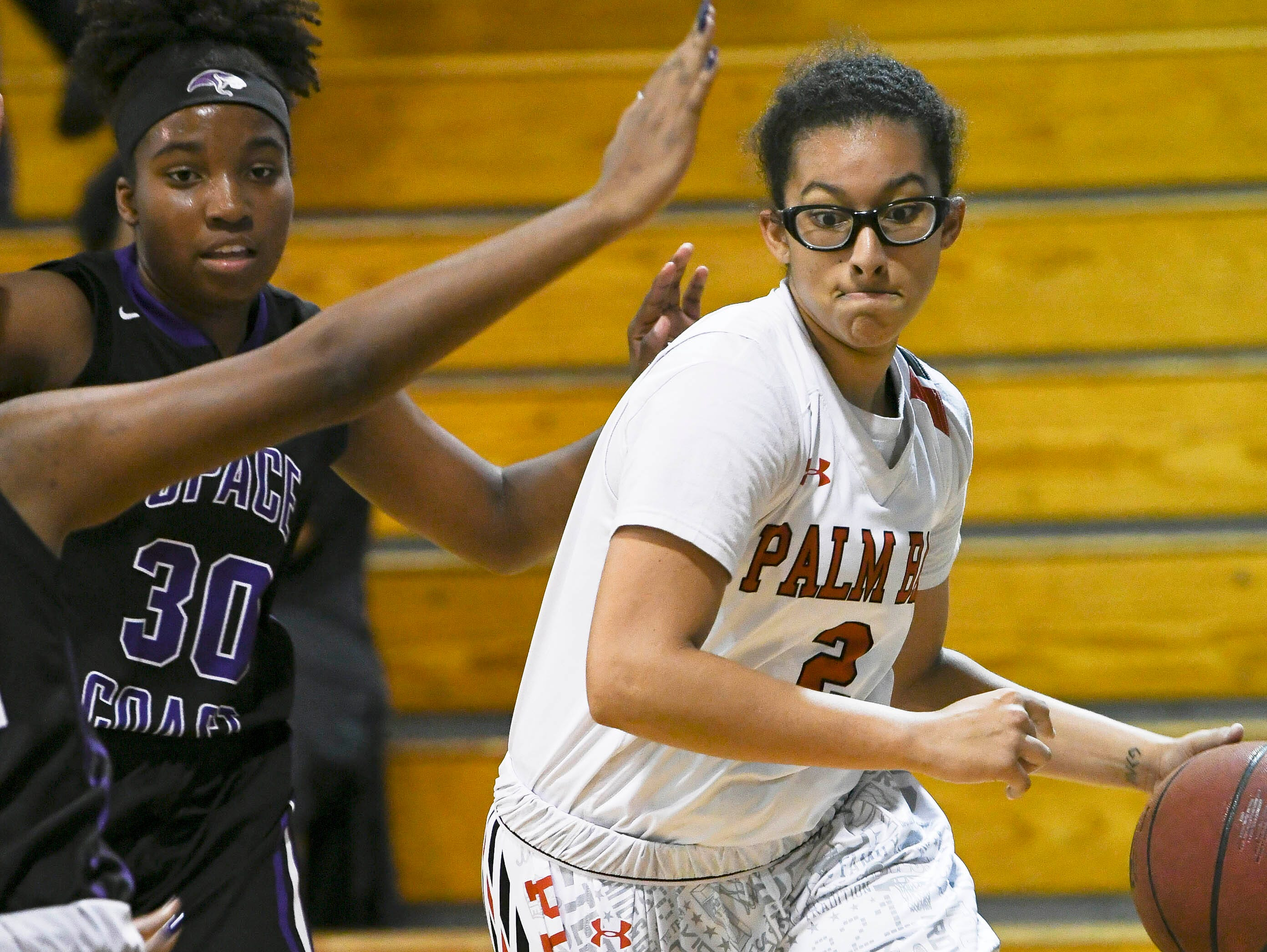 Palm Bay's Mary Penland-Holmes dribbles around Kaili Thomas Brooks of Space Coast during Thursday's District 14-6A basketball tournament at Rockledge High School.