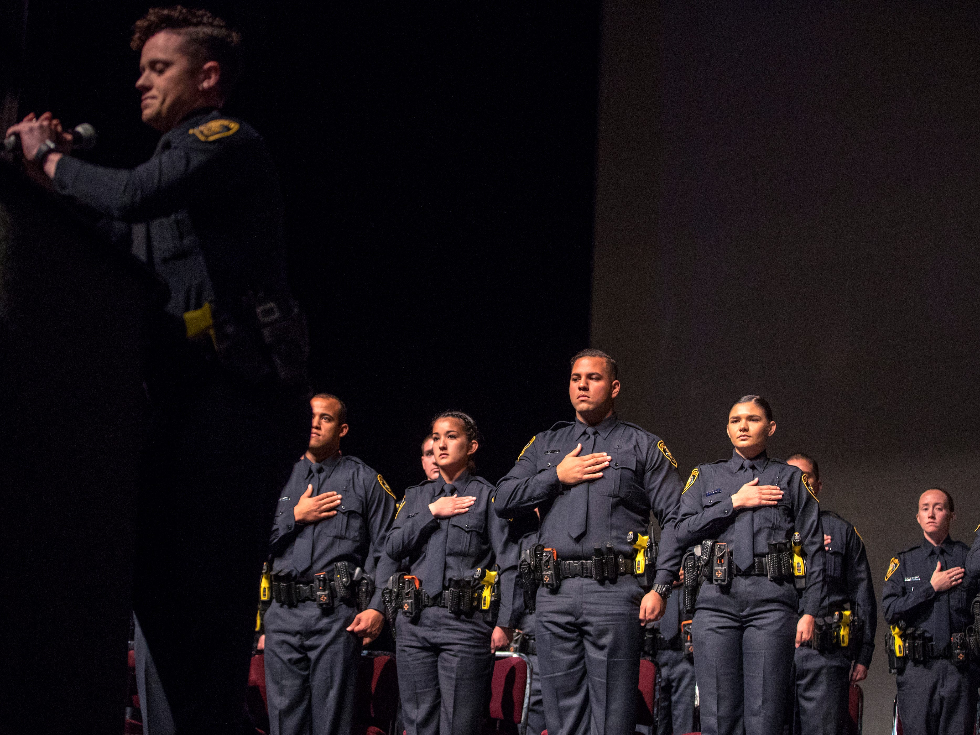 The 77th Corpus Christi Police Department Police Academy Graduates place their hands over their hearts during the National Anthem during their graduation ceremony at Selena Auditorium on Friday, February, 8, 2019.