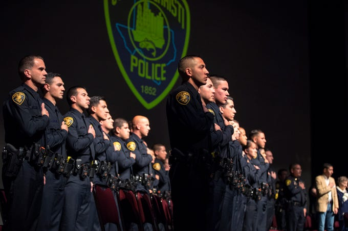 The 77th Corpus Christi Police Department Police Academy Graduates place their hands over their hearts as the colors are posted during their graduation ceremony at Selena Auditorium on Friday, February, 8, 2019.