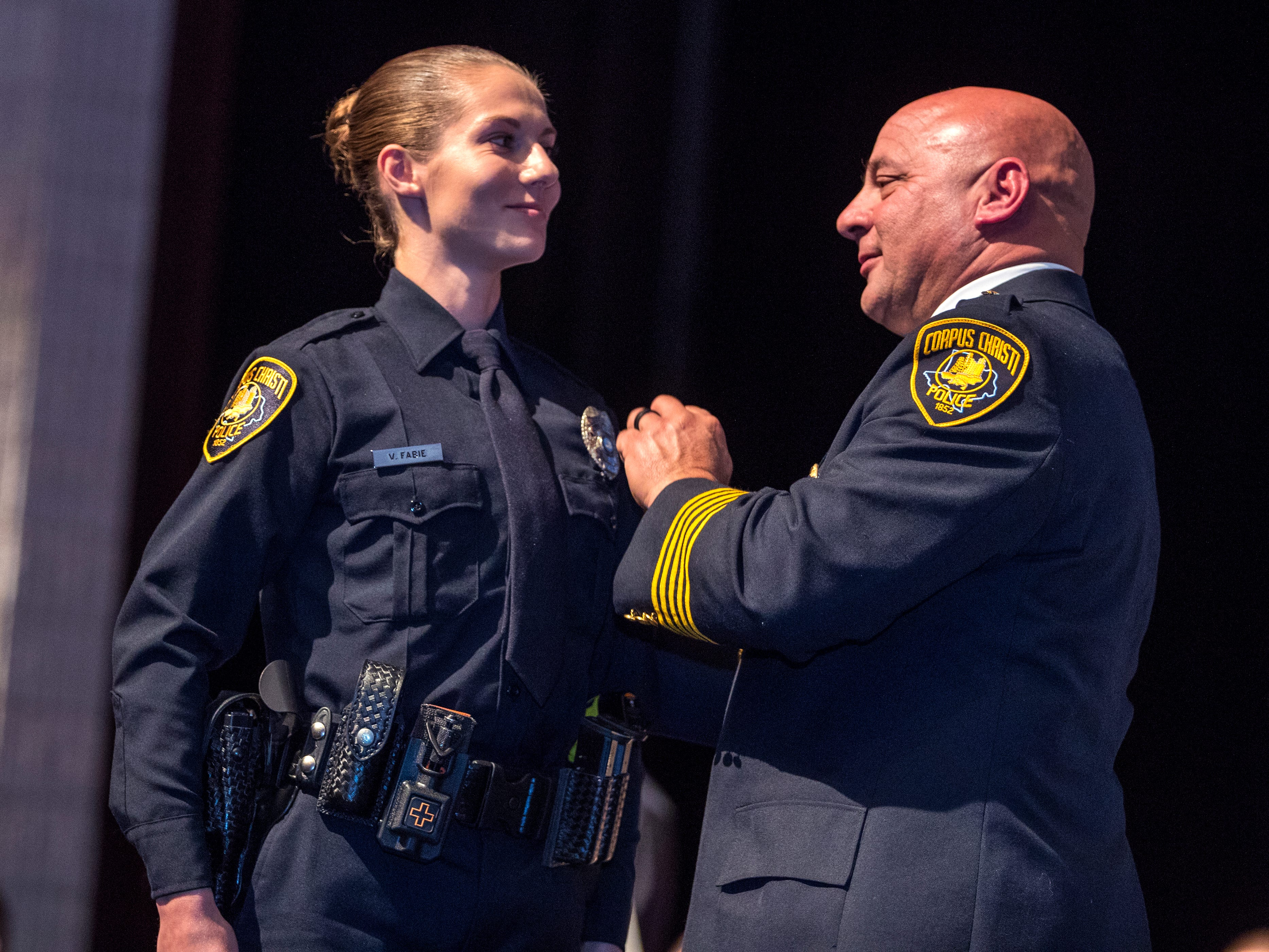 Victoria Fabie (left) receives her badge from Police Chief Mike Markle during the 77th Corpus Christi Police Department Police Academy Graduates' graduation ceremony at Selena Auditorium on Friday, February, 8, 2019.