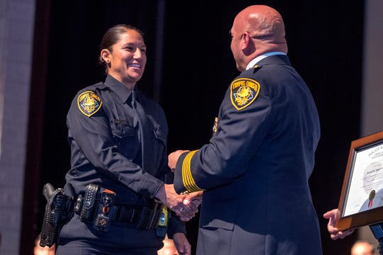 Jacqueline DeLeon (left) receives her badge from Police Chief Mike Markle during the 77th Corpus Christi Police Department Police Academy Graduates' graduation ceremony at Selena Auditorium on Friday, February, 8, 2019.