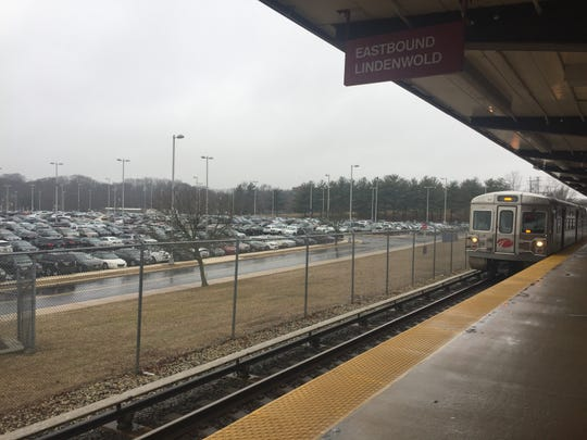 A PATCO Hi-Speedline train passes by one section of the expansive parking area at Woodcrest Station in Cherry Hill as it heads east to Lindenwold from Philadelphia. Covered parking is coming to this station and to PATCO in Lindenwold, Ashland in Voorhees and Ferry Avenue, Camden.