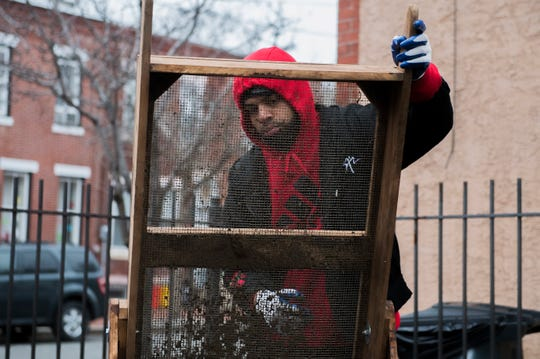 Senior Kofi Ries empties a sifter Thursday, Feb. 7, 2019 behind the Rutgers-Camden Office of Civic Engagement in Camden, N.J.