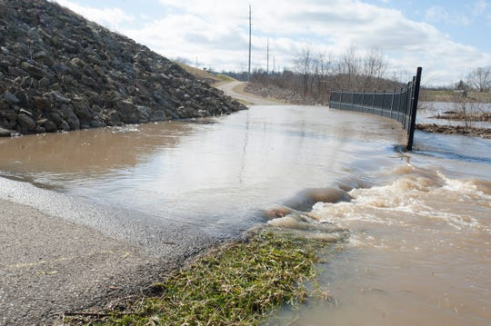 Melting snow and rain from the past few days caused the rushing waters of the Scioto River to flood the walking path underneath the Bridge St. bridge Friday afternoon in Chillicothe.