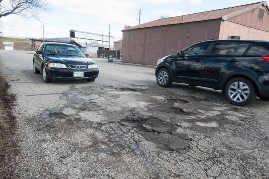 A motorist waits as another car avoids the potholes on Enderlin Circle inside Yoctangee Park Friday afternoon in Chillicothe.