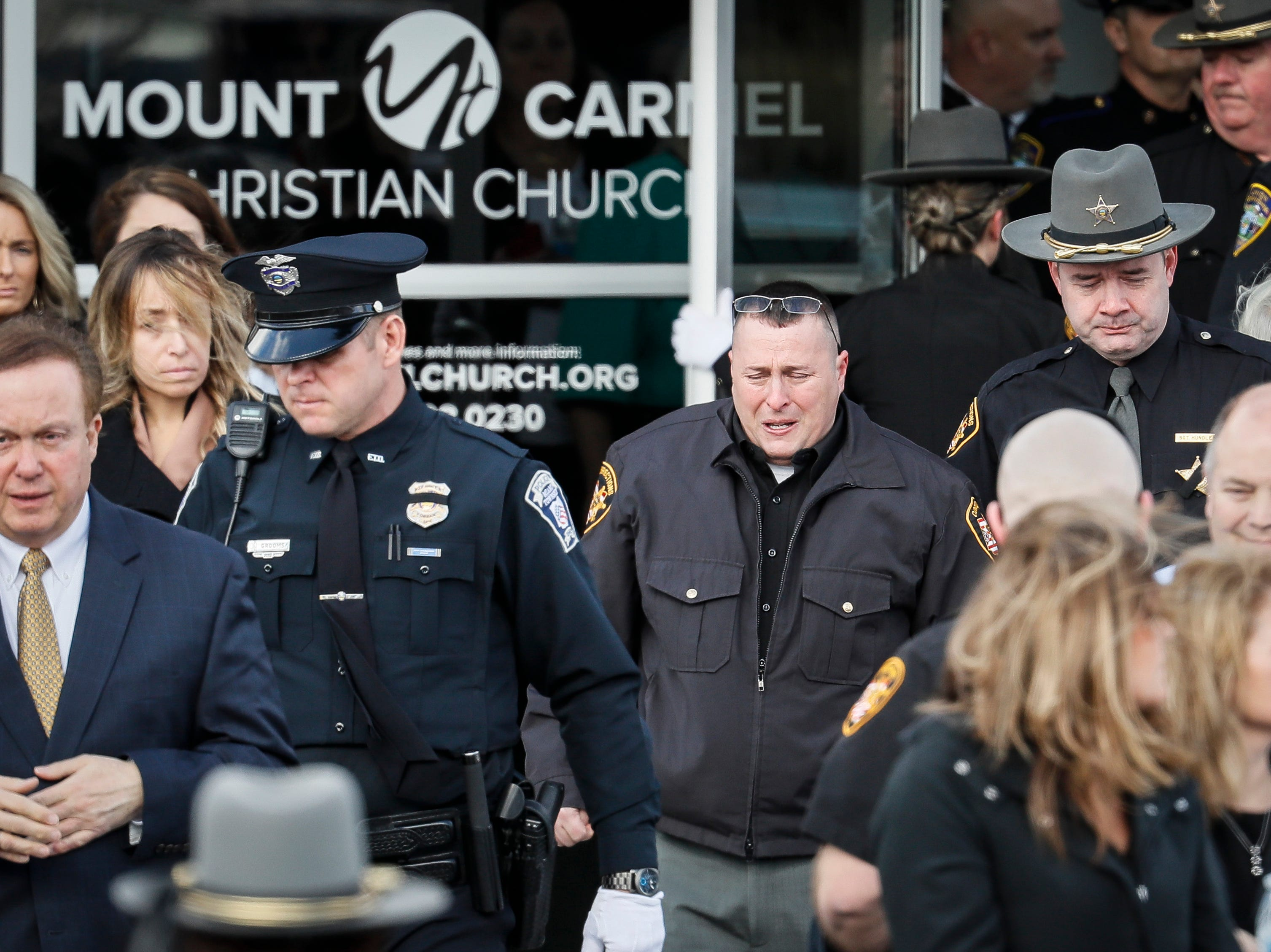 Officers react after the casket of Detective Bill Brewer, a 20-year veteran of the Clermont County Sheriff's Office, is placed into a hearse outside of Mt. Carmel Christian Church during funeral ceremonies, Friday, Feb. 8, 2019, in Batavia, Ohio. Authorities in the Cincinnati region are reeling after the deaths of five police officers in less than two months. (AP Photo/John Minchillo)