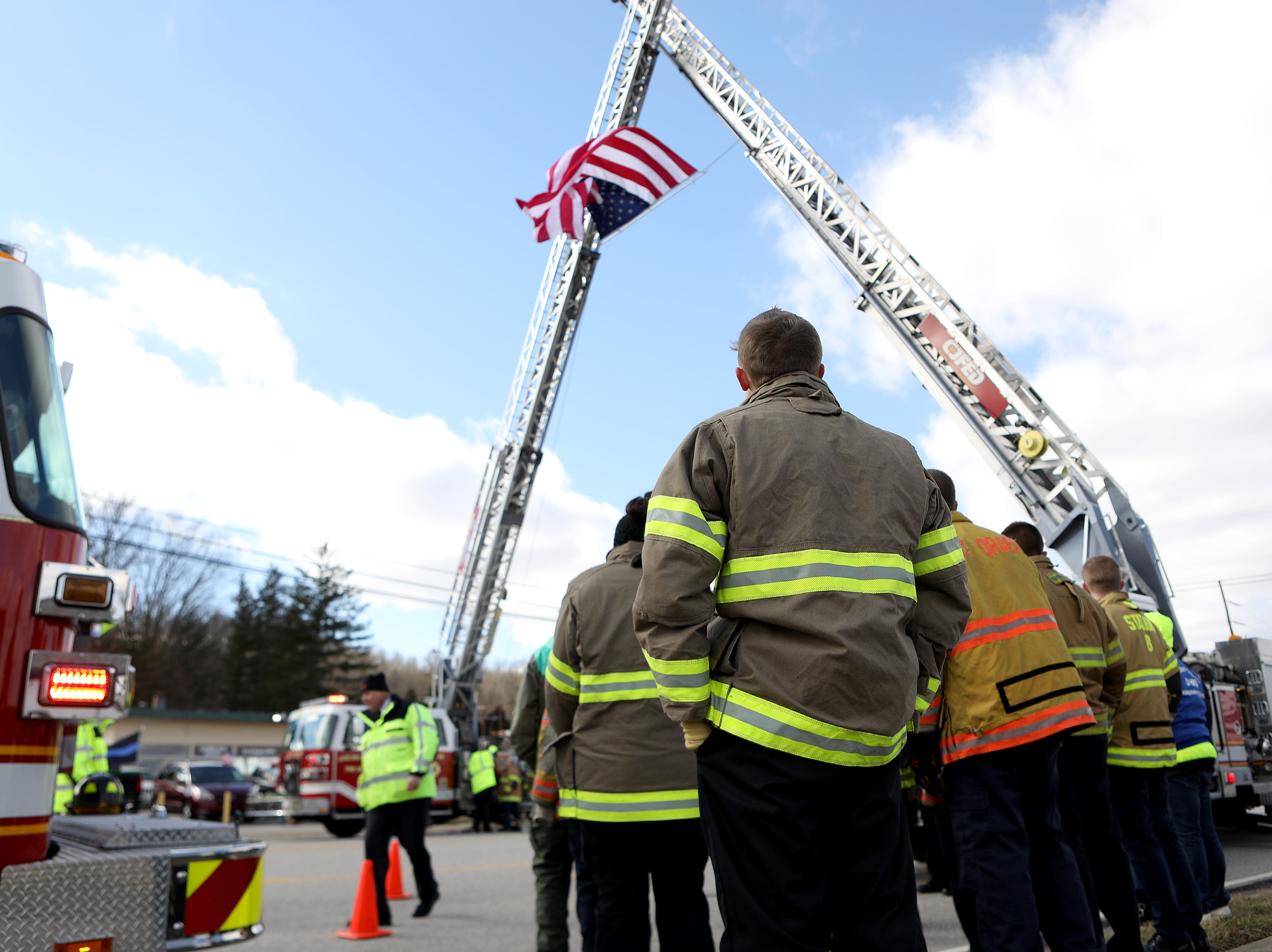 Firefighters line Main Street in Batavia  as they wait for the procession.