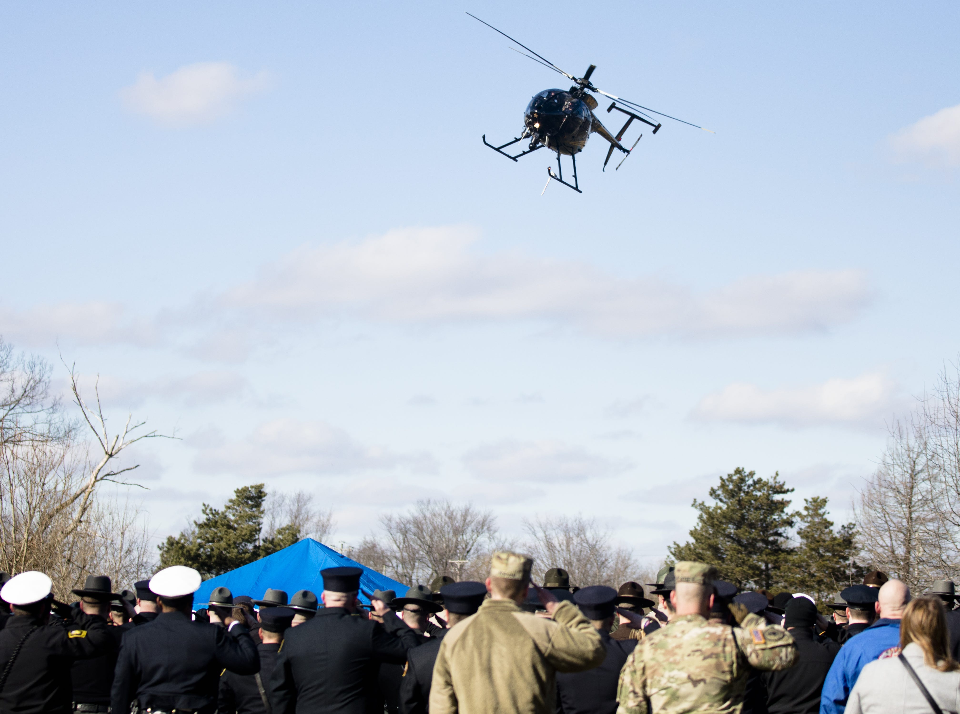 A helicopter performs a fly over during the burial service of Detective Bill Brewer, a 20-year veteran of the Clermont County Sheriff's Office, on Friday, Feb. 8, 2019, at Pierce Township Cemetery in Cincinnati. Brewer, 42, of Pierce Township, died in the line of duty. He was shot Feb. 2 during a standoff. Deputy Brewer is survived by a wife and 5-year-old son.