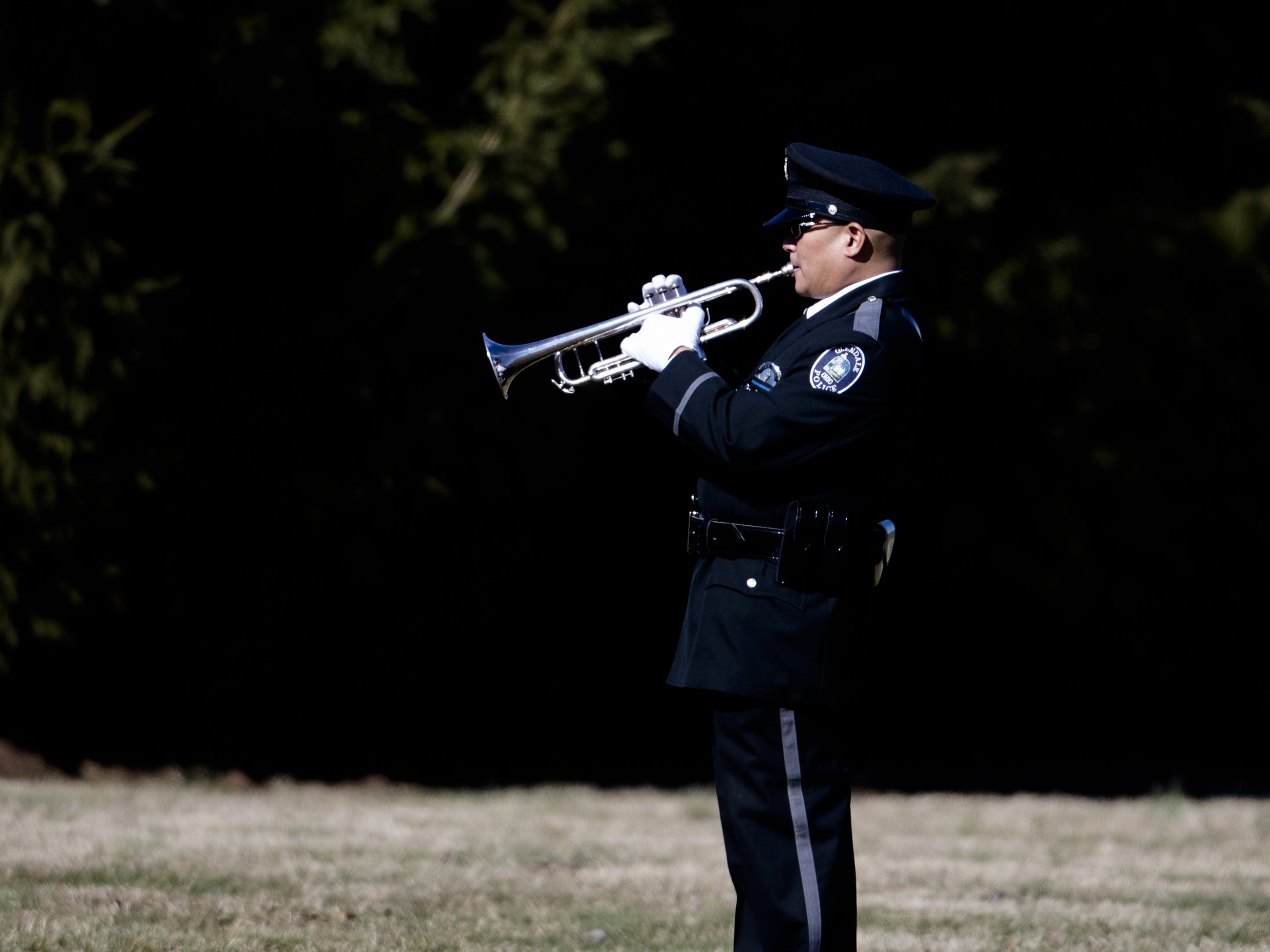 An officer practices playing TAPS before the burial service of Detective Bill Brewer, a 20-year veteran of the Clermont County Sheriff's Office, on Friday, Feb. 8, 2019, at Pierce Township Cemetery in Cincinnati. Brewer, 42, of Pierce Township, died in the line of duty. He was shot Feb. 2 during a standoff. Deputy Brewer is survived by a wife and 5-year-old son.