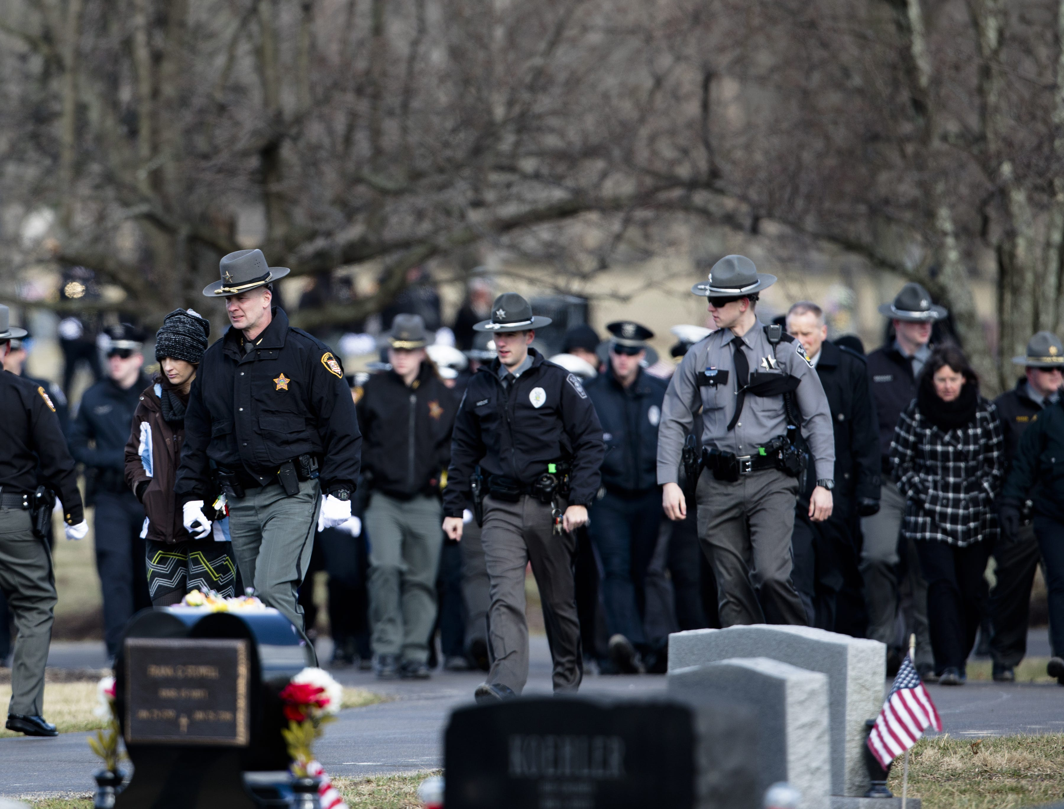 Family, friends and fellow police officers arrive for the burial service of Detective Bill Brewer, a 20-year veteran of the Clermont County Sheriff's Office, on Friday, Feb. 8, 2019, at Pierce Township Cemetery in Cincinnati. Brewer, 42, of Pierce Township, died in the line of duty. He was shot Feb. 2 during a standoff. Deputy Brewer is survived by a wife and 5-year-old son.