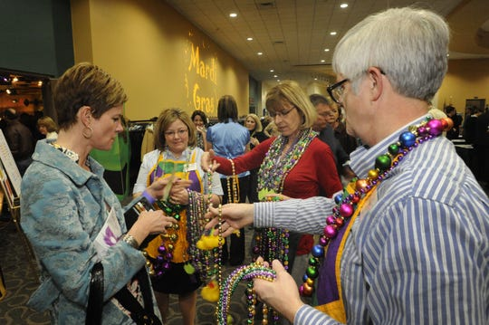 A group of people select beads at a past Mardi Gras for Homeless Children gala fundraiser at the Northern Kentucky Convention Center in Covington. The event raises money for three nonprofits in Northern Kentucky assisting homeless children.