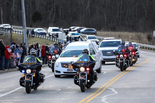 Crowds gather to observe the procession of Detective Bill Brewer as his body is moved through the communities in Clermont County he protected on the way to the funeral. Many carry flags and signs sharing their support for the police and thanking Officer Brewer for his service.