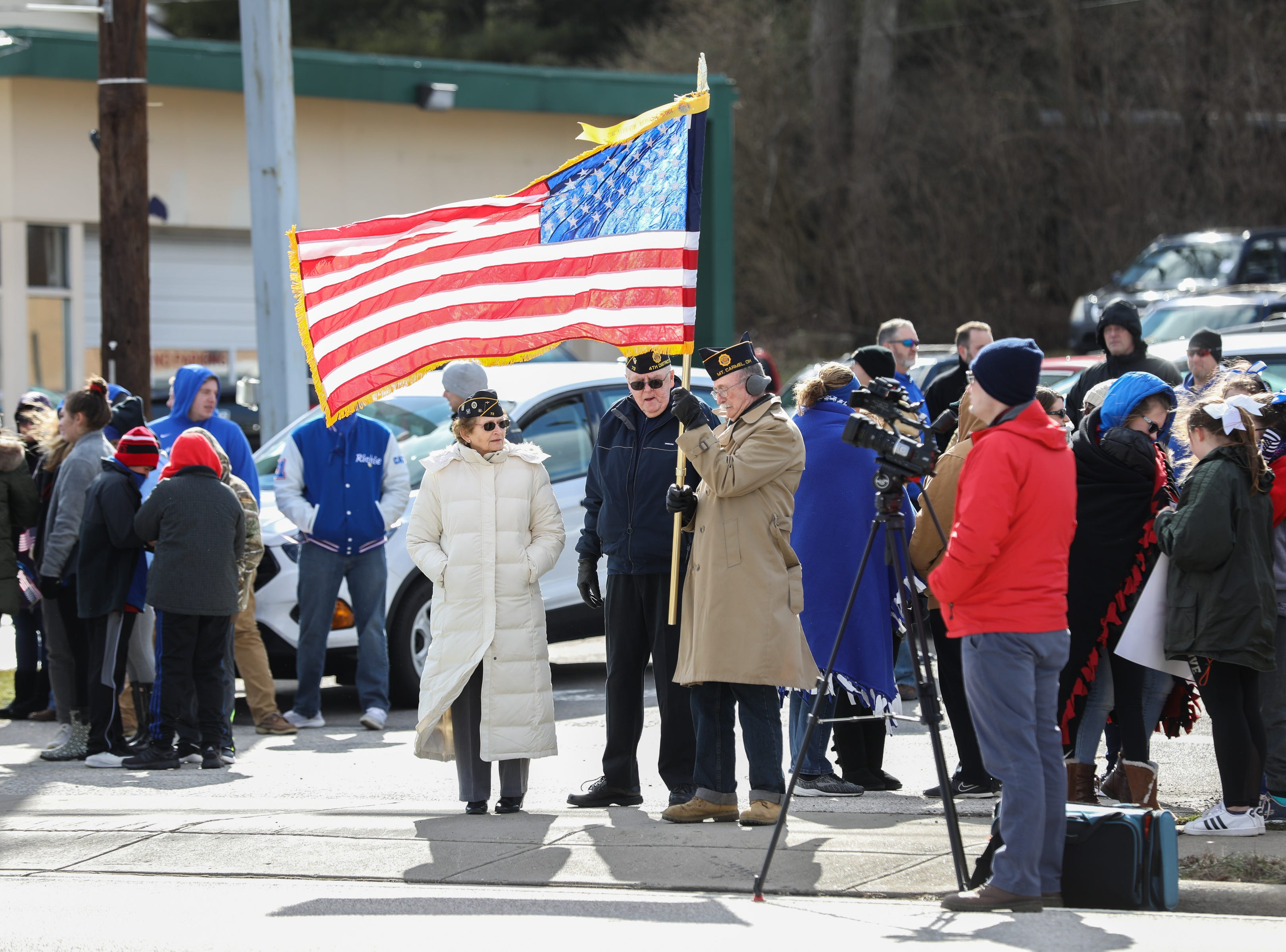 Crowds gather to observe the procession of Detective Bill Brewer as his body is moved through the communities he protected on the way to the funeral. Many carry flags and signs sharing their support for the police and thanking Officer Brewer for his service.