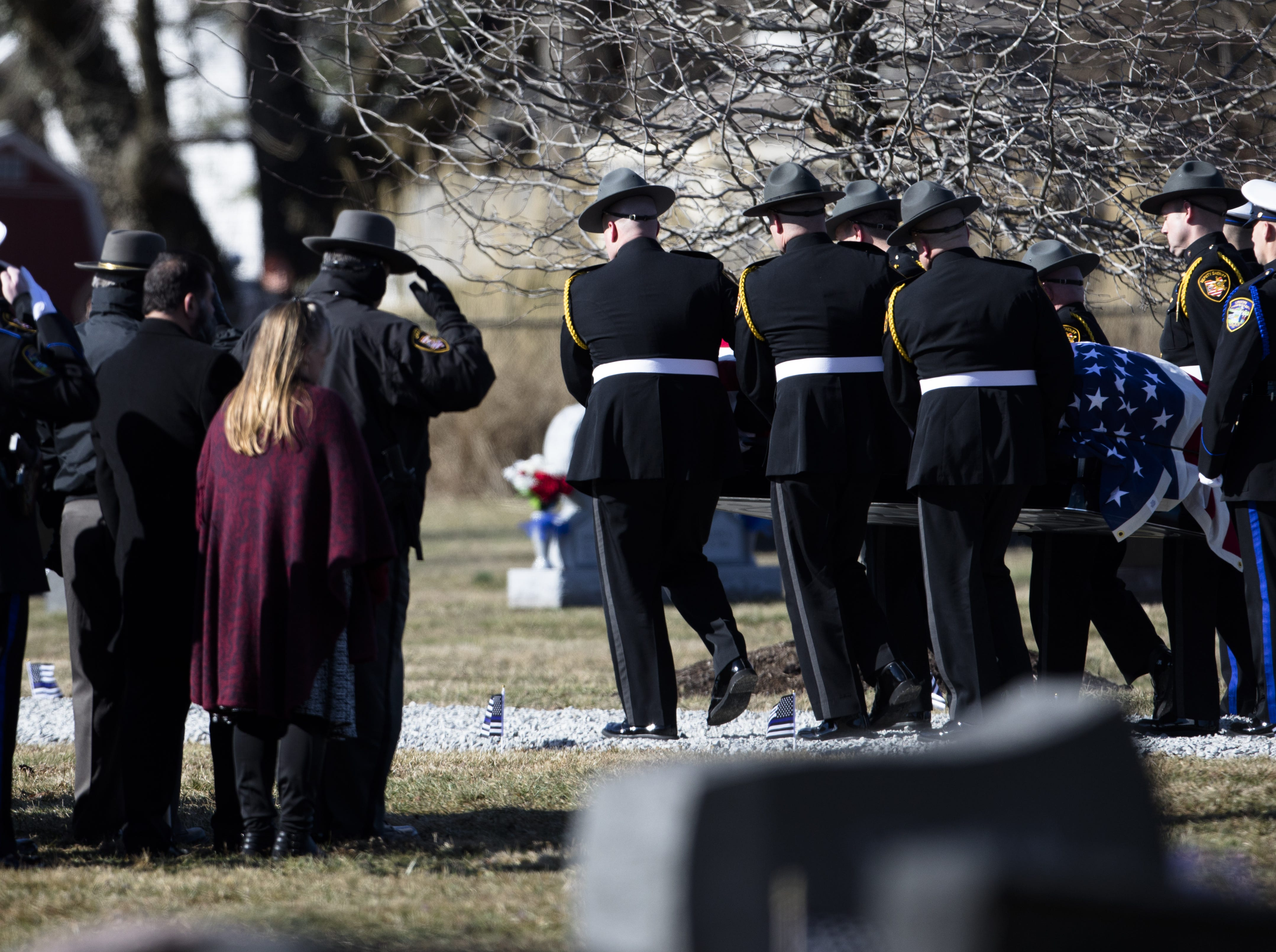 Pallbearers carry the casket bearing Detective Bill Brewer, a 20-year veteran of the Clermont County Sheriff's Office, is processed through Pierce Township Cemetery in a Caisson on Friday, Feb. 8, 2019, at in Cincinnati. Brewer, 42, of Pierce Township, died in the line of duty. He was shot Feb. 2 during a standoff. Deputy Brewer is survived by a wife and 5-year-old son.
