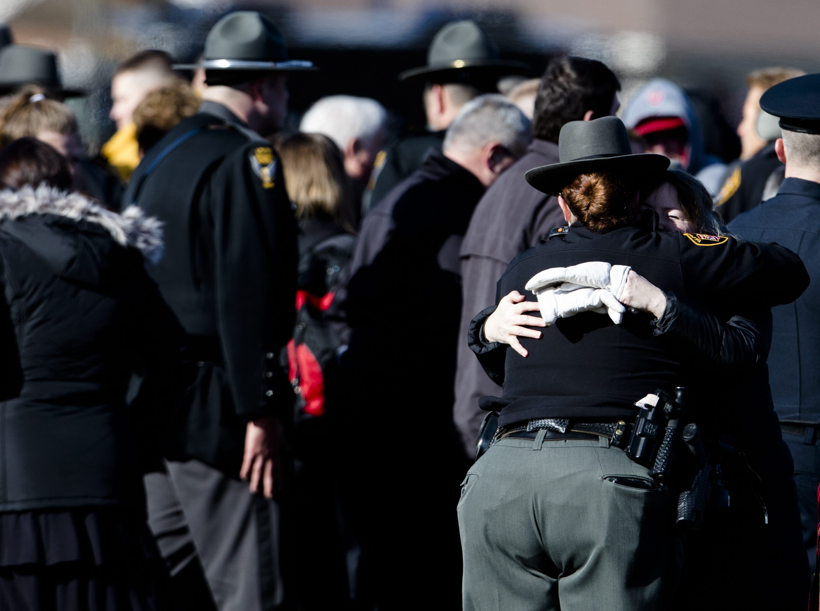 People embrace after the burial service of Detective Bill Brewer, a 20-year veteran of the Clermont County Sheriff's Office, on Friday, Feb. 8, 2019, at Pierce Township Cemetery in Cincinnati. Brewer, 42, of Pierce Township, died in the line of duty. He was shot Feb. 2 during a standoff. Deputy Brewer is survived by a wife and 5-year-old son.