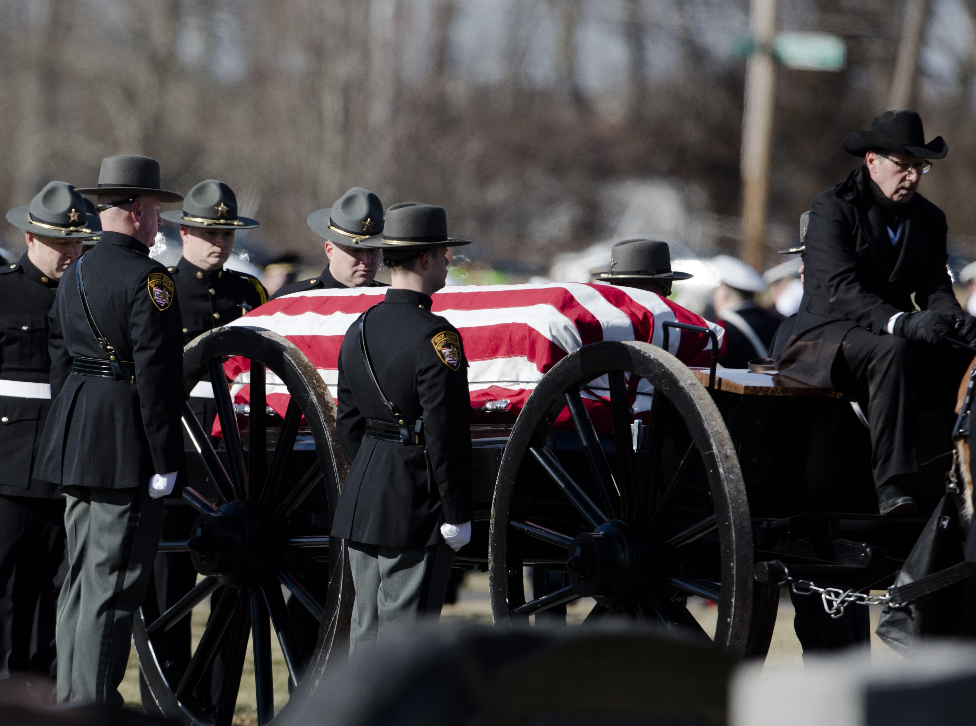 The casket carrying Detective Bill Brewer, a 20-year veteran of the Clermont County Sheriff's Office, is processed through Pierce Township Cemetery in a Caisson on Friday, Feb. 8, 2019, at in Cincinnati. Brewer, 42, of Pierce Township, died in the line of duty. He was shot Feb. 2 during a standoff. Deputy Brewer is survived by a wife and 5-year-old son.
