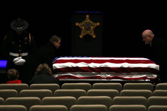 The casket of Clermont County Sheriff's Detective William Lee Brewer Jr. is placed as his son, Braxton, 5, and wife, Jamie, sit in attendance ahead of funeral services, Friday, Feb. 8, 2019, at Mount Carmel Christian Church in Union Township, Ohio. Brewer, a 20-year veteran of the Clermont County SheriffÕs Office, died in the line of duty. He was shot Feb. 2 during a standoff. Brewer, 42, of Pierce Township, is survived by his wife, Jamie, and a 5-year-old son, Braxton. (Kareem Elgazzar/The Cincinnati Enquirer)