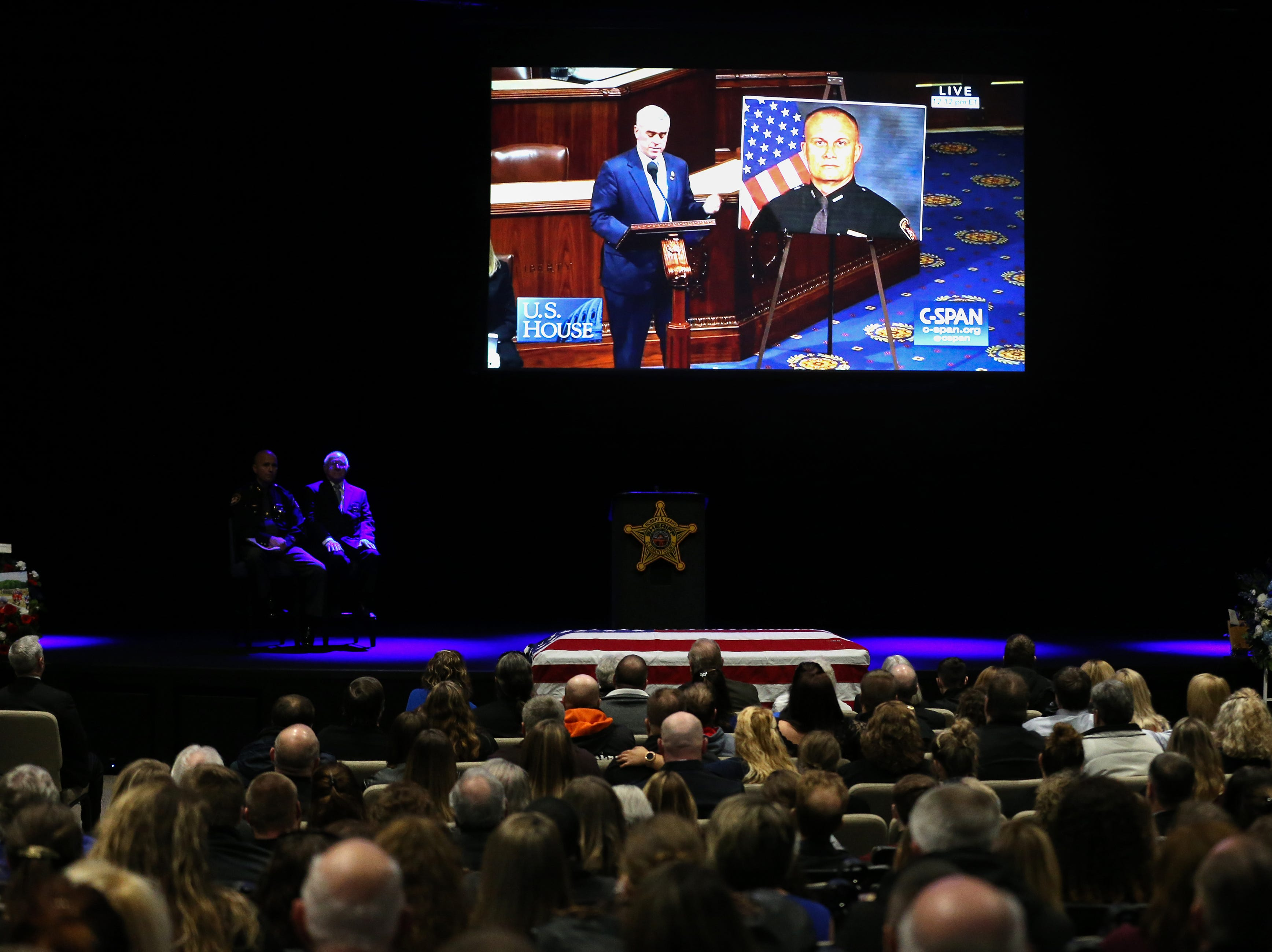 A video message is played featuring U.S. Rep. Brad Wenstrup on the floor of the House of Representatives during funeral services for Clermont County Sheriff's Detective William Lee Brewer Jr., Friday, Feb. 8, 2019, at Mount Carmel Christian Church in Union Township, Ohio. Brewer, a 20-year veteran of the Clermont County Sheriff's Office, died in the line of duty. He was shot Feb. 2 during a standoff.
