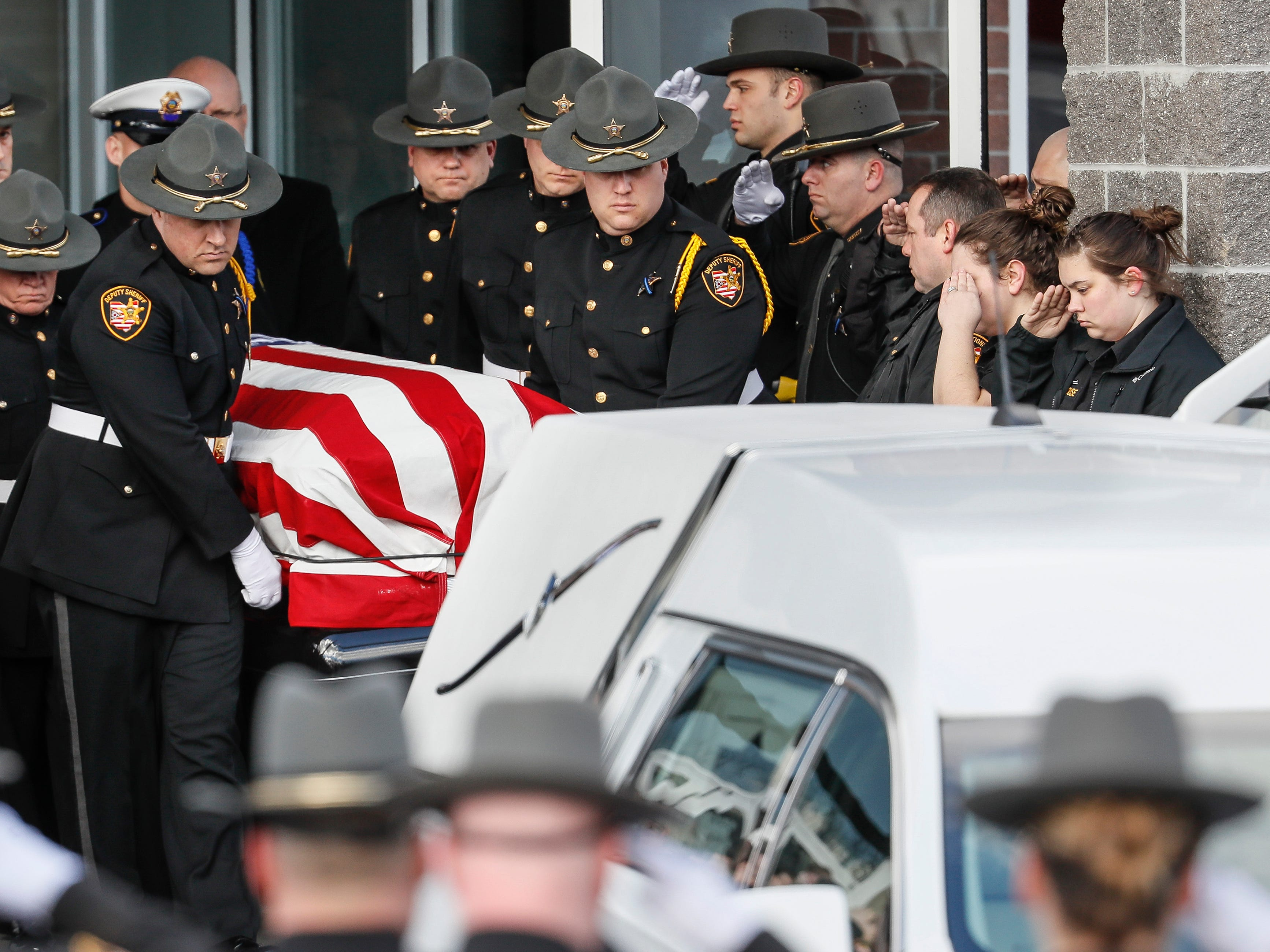 The casket of Detective Bill Brewer, a 20-year veteran of the Clermont County Sheriff's Office, is brought out of Mt. Carmel Christian Church during funeral ceremonies, Friday, Feb. 8, 2019, in Batavia, Ohio. Authorities in the Cincinnati region are reeling after the deaths of five police officers in less than two months. (AP Photo/John Minchillo)