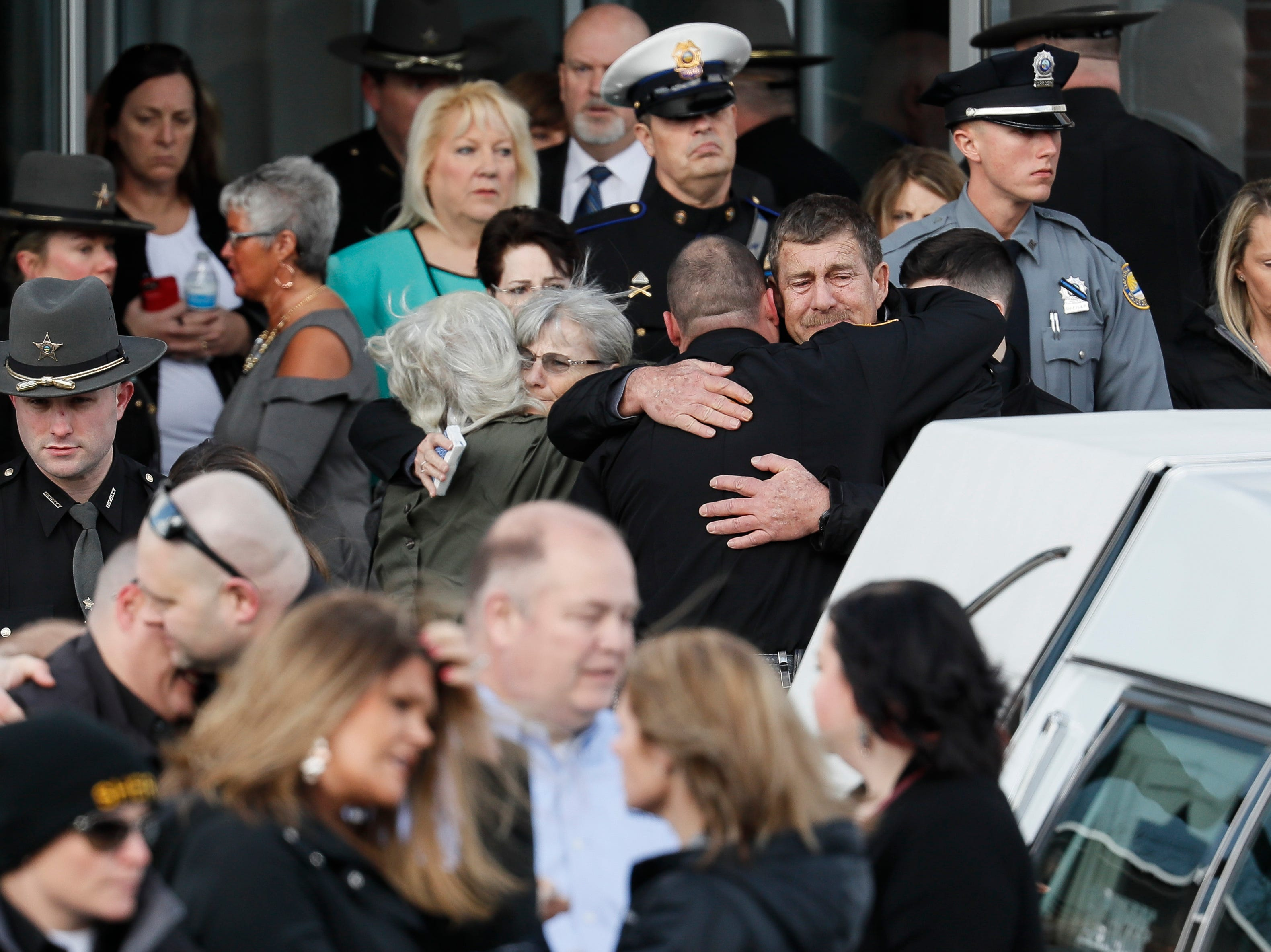 Officers and mourners react after the casket of Detective Bill Brewer, a 20-year veteran of the Clermont County Sheriff's Office, is placed into a hearse outside of Mt. Carmel Christian Church during funeral ceremonies, Friday, Feb. 8, 2019, in Batavia, Ohio. Authorities in the Cincinnati region are reeling after the deaths of five police officers in less than two months. (AP Photo/John Minchillo)