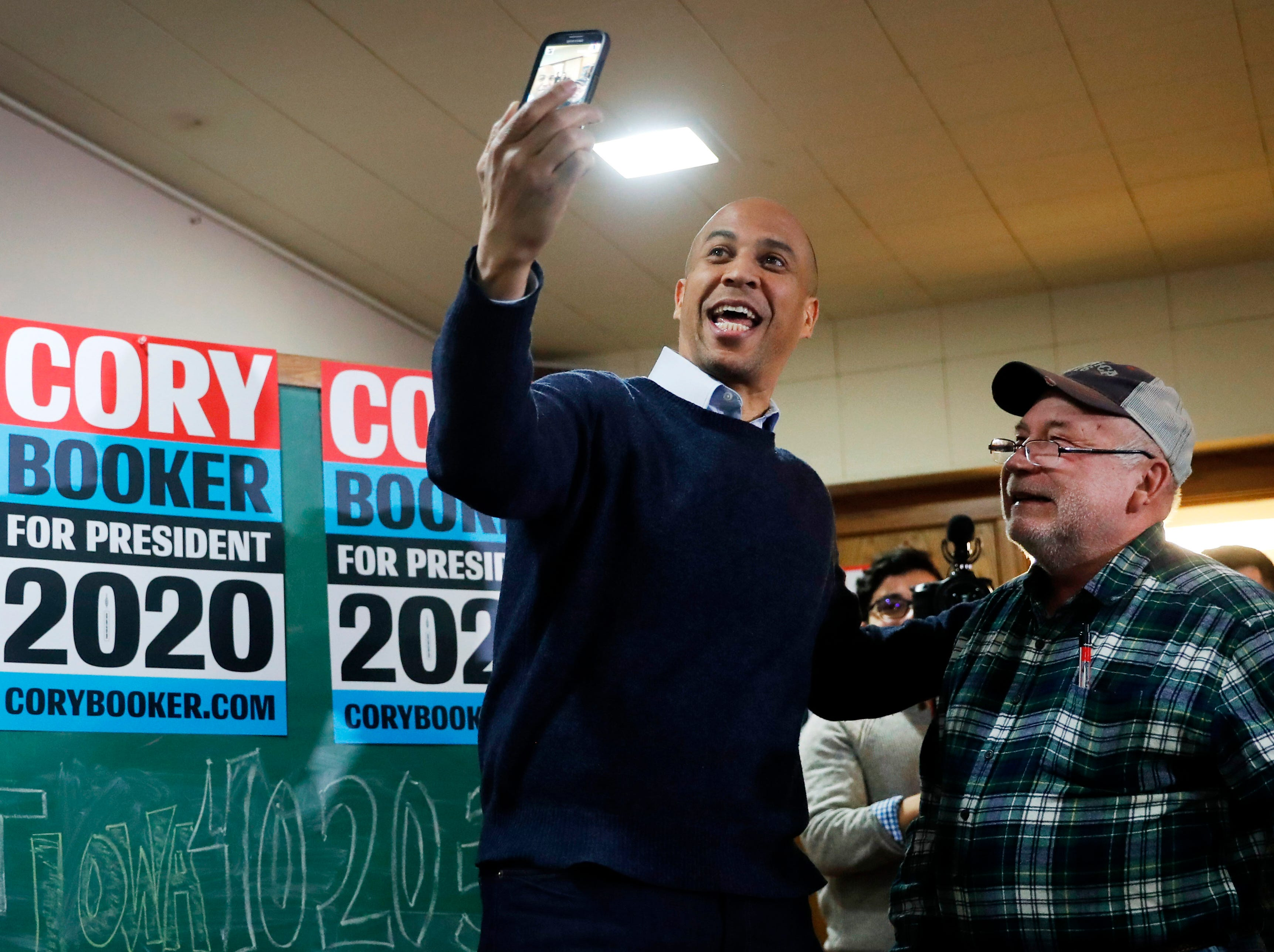 U.S. Sen. Cory Booker, D-N.J., poses for a photo with Chris Peterson, of Clear Lake, Iowa, right, during a meet and greet with local residents at the First Congregational United Church of Christ, Friday, Feb. 8, 2019, in Mason City, Iowa. (AP Photo/Charlie Neibergall)