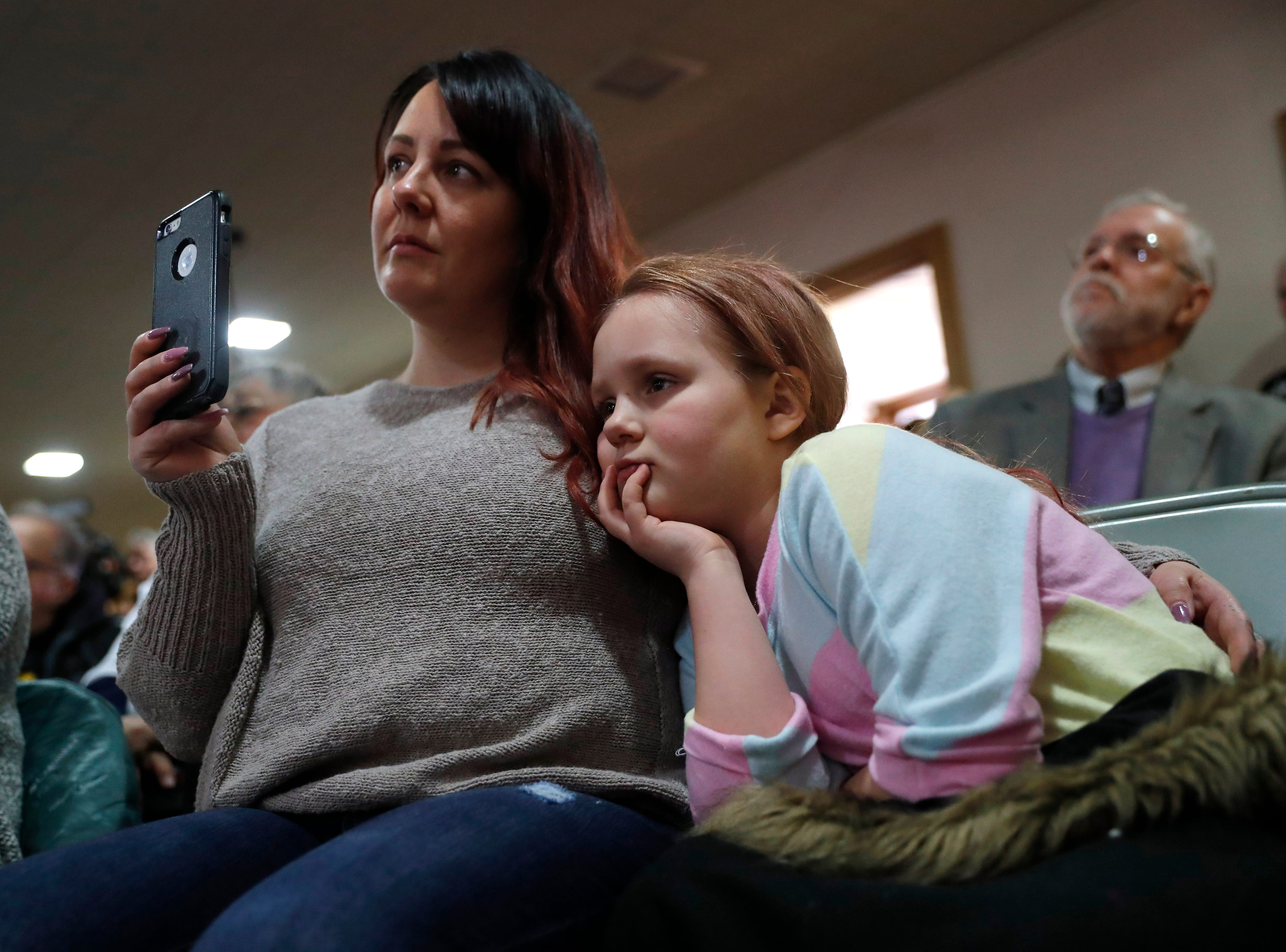 Alyssa Benson, of Mason City, Iowa, and her daughter Jersey, right, listen to U.S. Sen. Cory Booker, D-N.J., speaks during a meet and greet at the First Congregational United Church of Christ, Friday, Feb. 8, 2019, in Mason City, Iowa. (AP Photo/Charlie Neibergall)