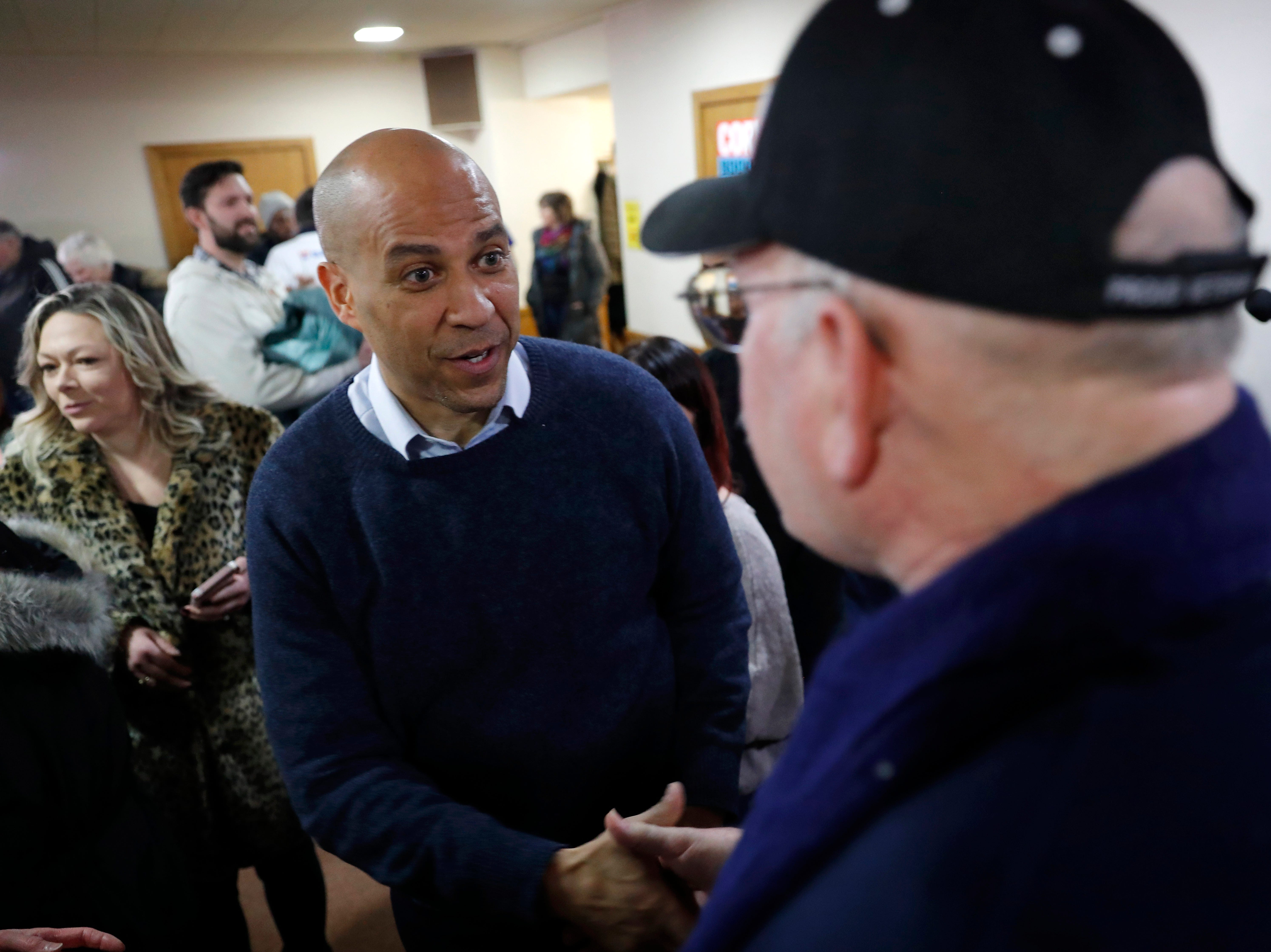 U.S. Sen. Cory Booker, D-N.J., speaks with Steven Howell, of Mason City, Iowa, right, during a meet and greet with local residents at the First Congregational United Church of Christ, Friday, Feb. 8, 2019, in Mason City, Iowa. (AP Photo/Charlie Neibergall)