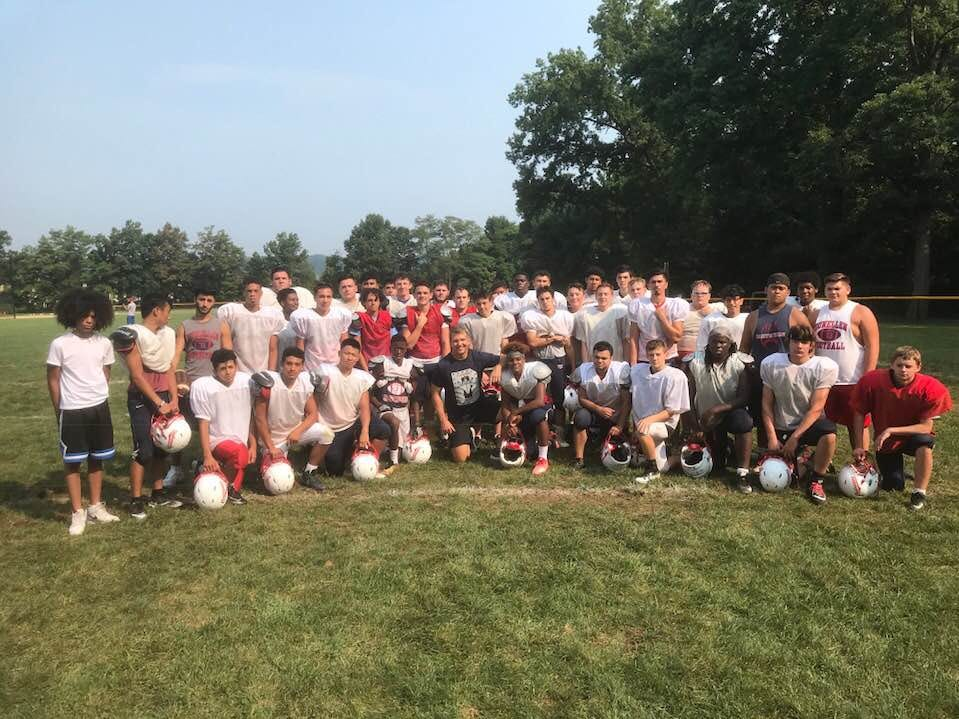 Dunellen Flag Rugby Director Chris Washburn, center, is pictured with the Dunellen High School Football team.
