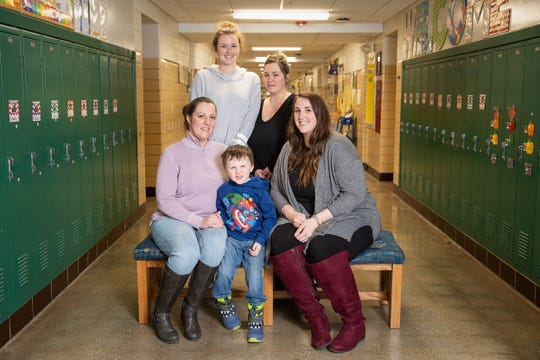Easton Peterson (center) with his mother Audra Peterson (left) and teacher Kati Grundey (right). Behind them are two other members of Woodlawn's preschool teaching team, Emily Ward and  Ashley Jeffers.