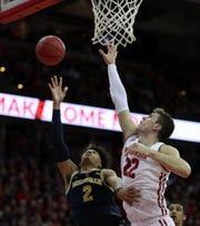 Michigan's Jordan Poole shoots as Wisconsin's Ethan Happ defends Jan. 19.