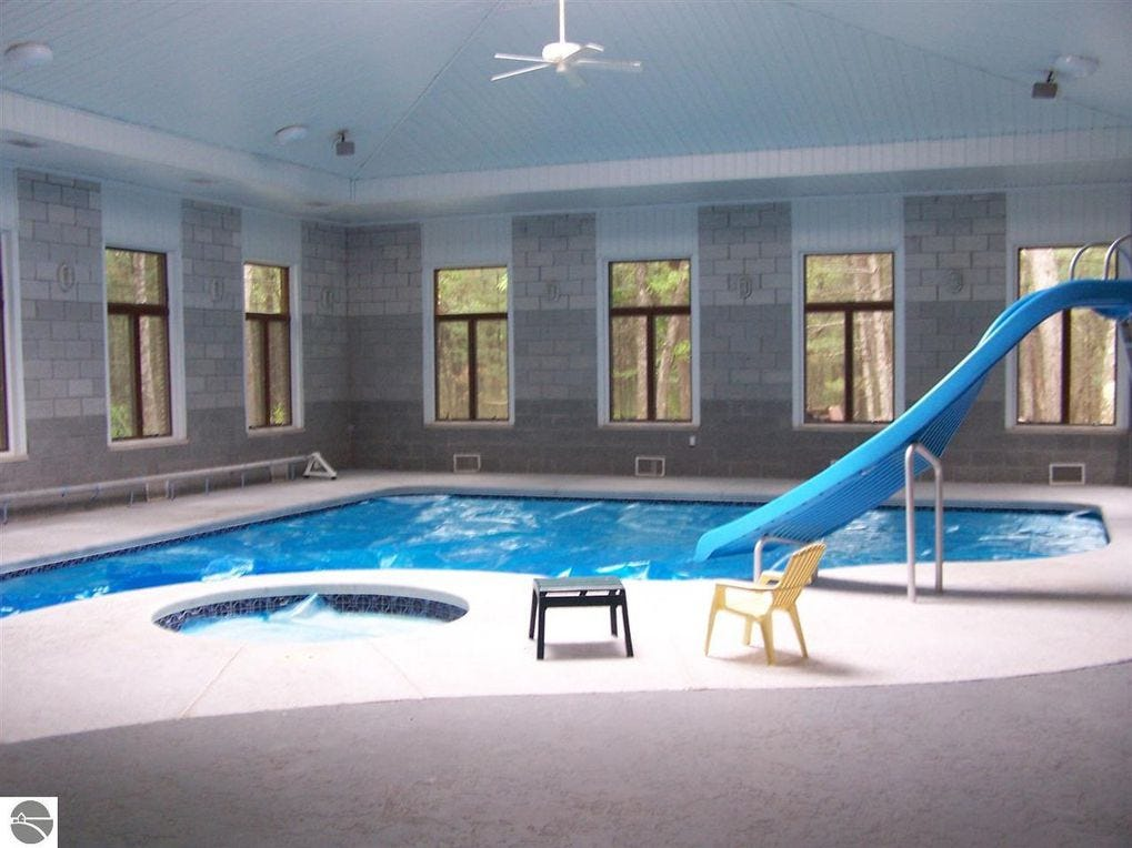 The home has an indoor pool with a slide and hot tub.