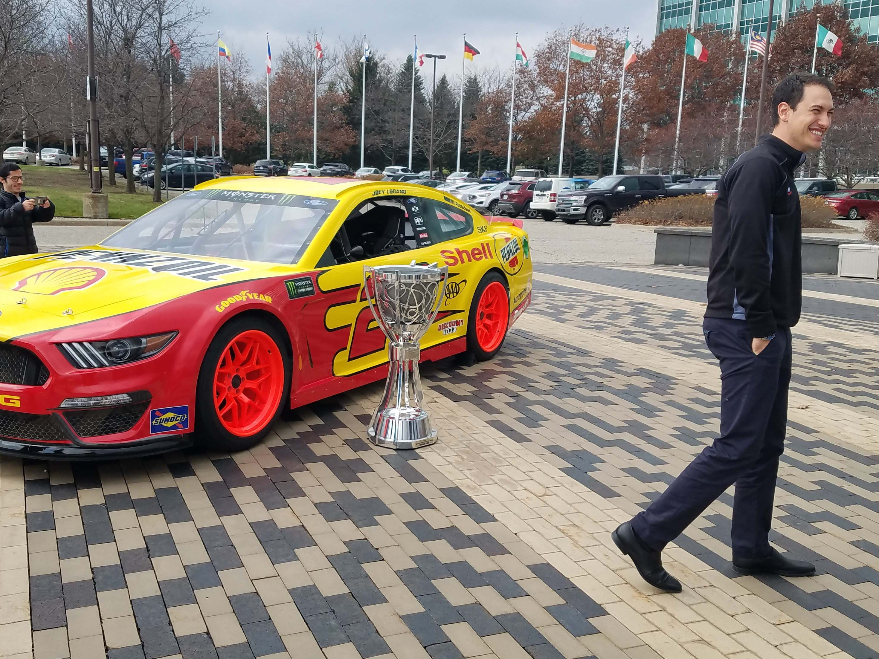 2018 NASCAR champ Joey Logano enjoys his victory gift - a NASCAR Ford Mustang drifter - in front of Ford HQ. Logano will compete for Team Penske in a new NASCAR Mustang at Daytona this month.