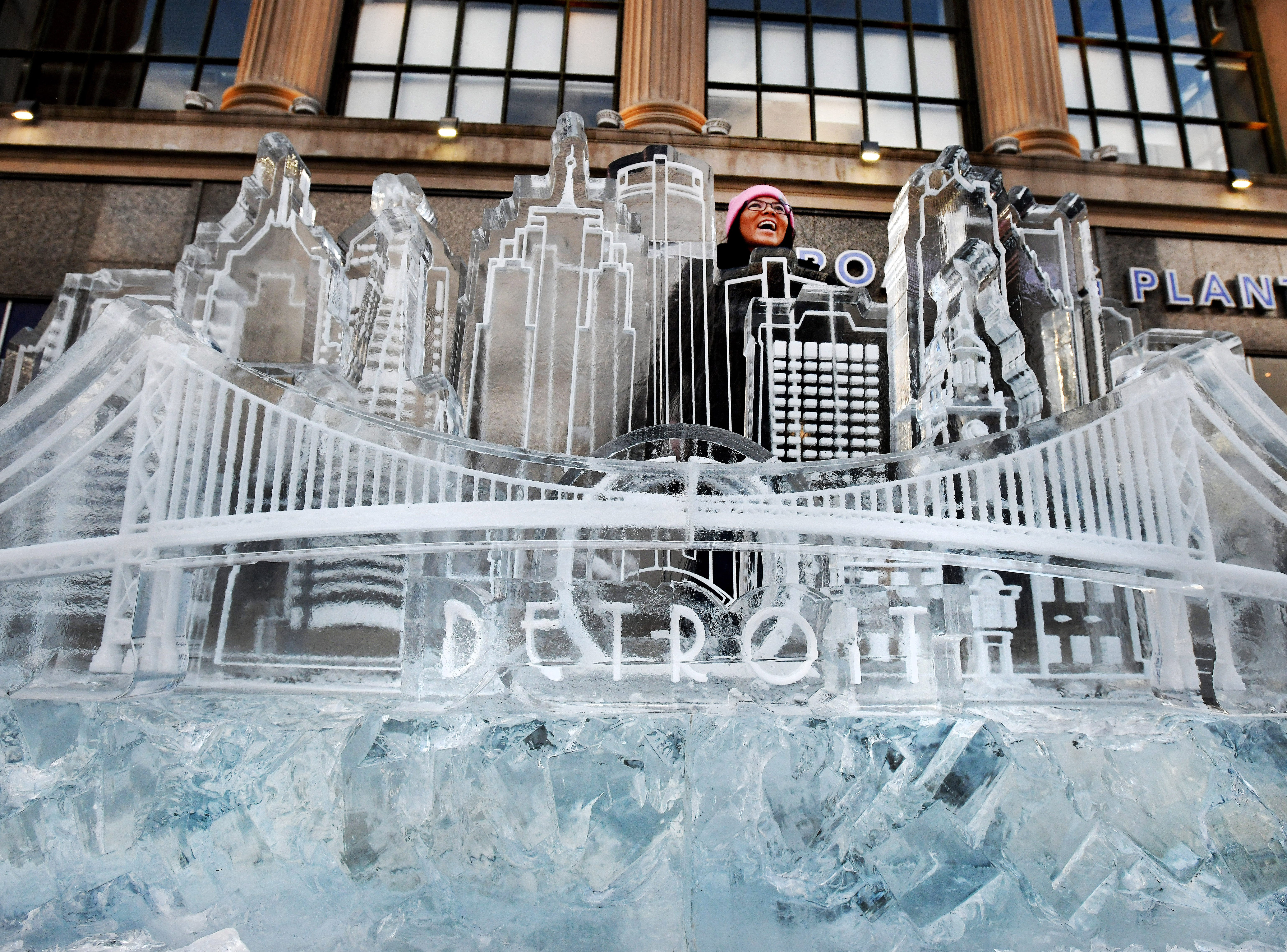 Detroiter Grace Albers braves the bitterly-cold winds to pose for a picture behind a Motown skyline ice sculpture created by US Ice Carvings for the 2019 Motown Winter Blast in Detroit, Michigan on February 8, 2019.