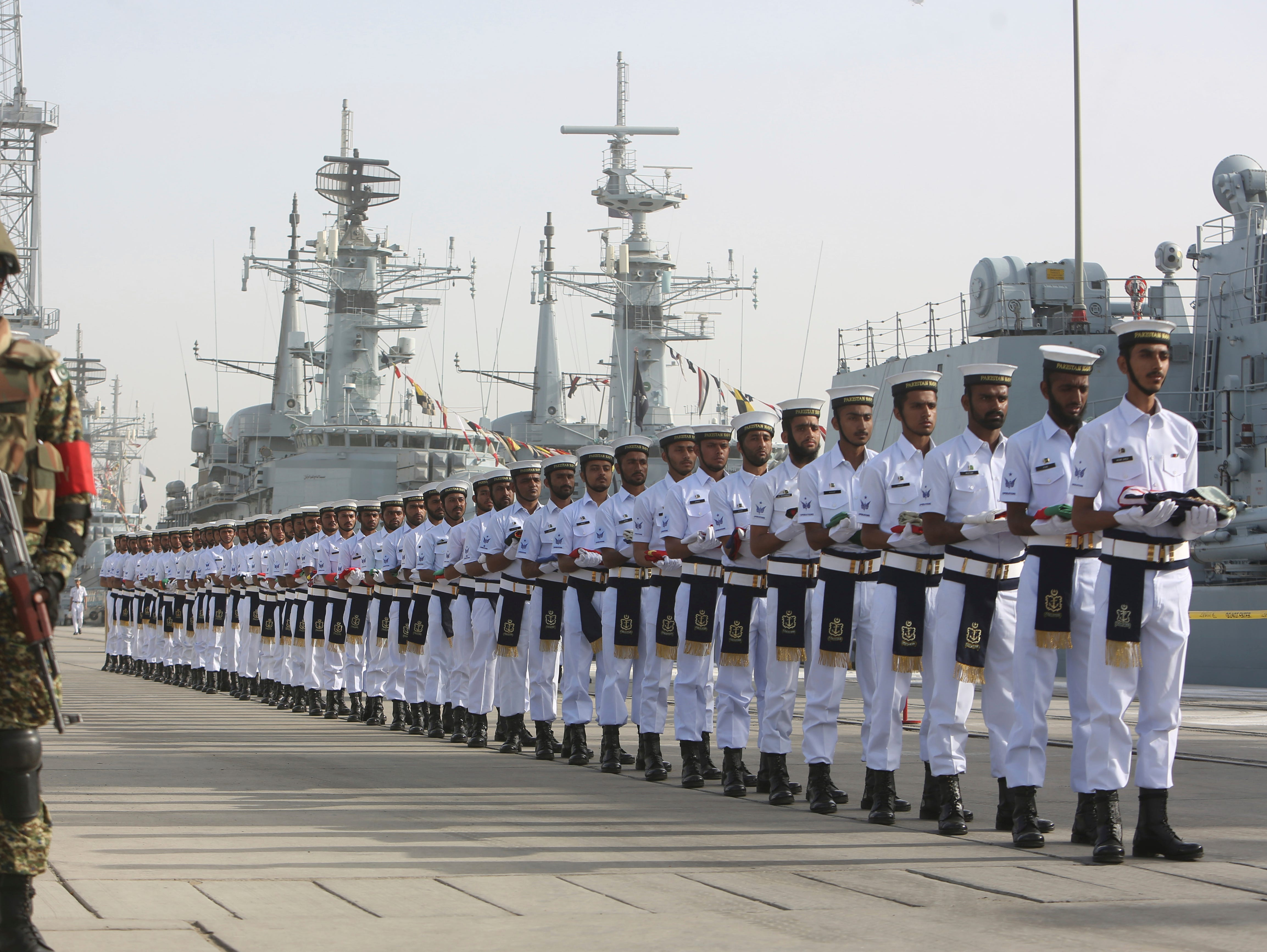 Pakistan Naval personal carry national flags of participating countries during the opening ceremony of Pakistan Navy's Multinational Exercise AMAN-19, in Karachi, Friday, Feb. 8, 2019. A five-day multinational exercise hhas begun near the southern port city of Karachi in an effort to enhance cooperation in keeping the seas safe from pirates, terrorists and smugglers.