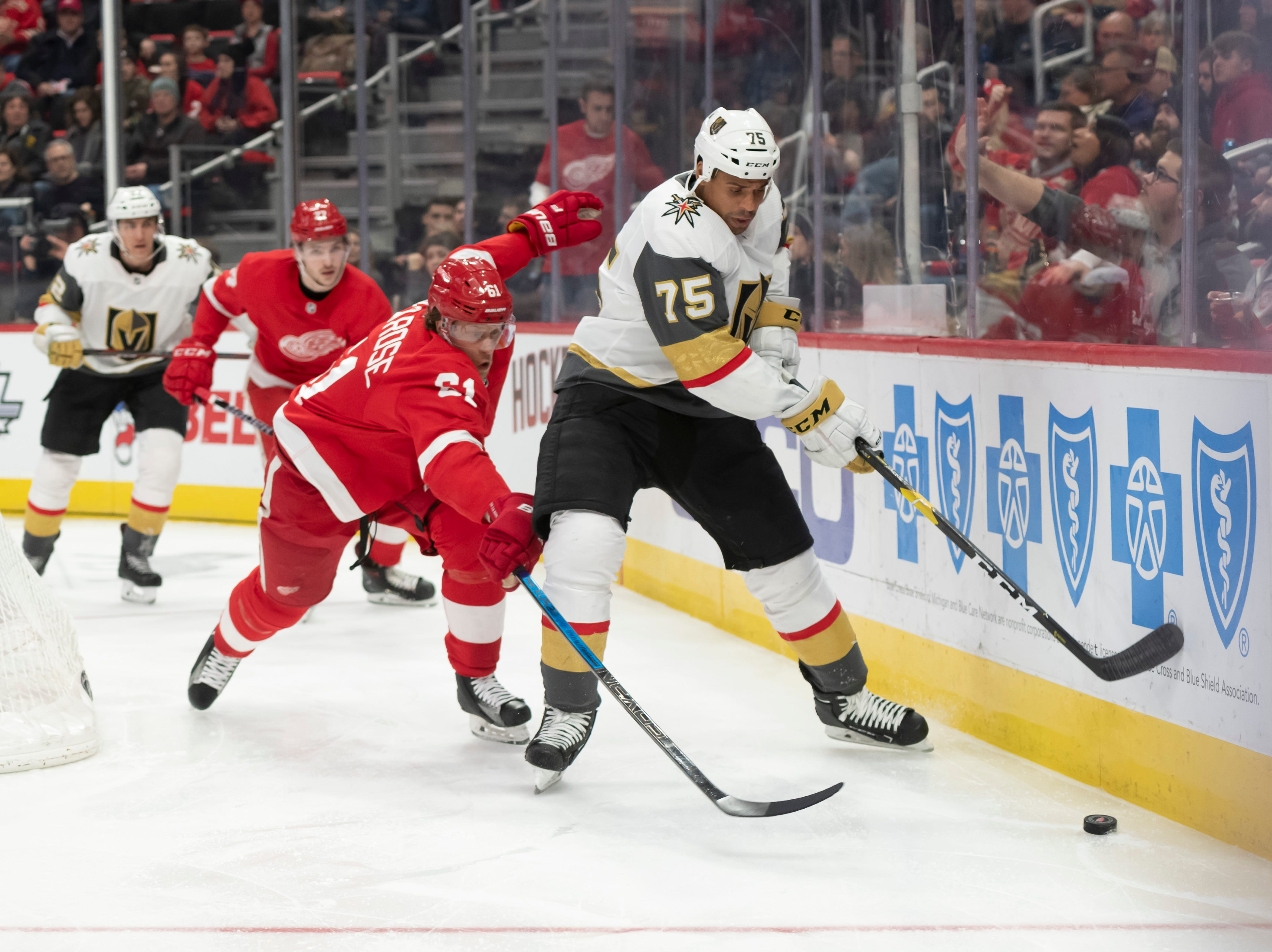 Detroit defenseman Dennis Cholowski tires to steal the puck away from Vegas right wing Ryan Reaves in the second period.