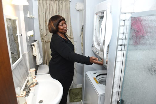 Bertha Alexander of Detroit shows the stacked washer/dryer unit in her lower level remodeled bathroom.