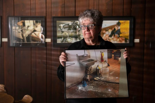 Former health inspector Agnes Gira holds a photo of an employee sink with no soap, above a gruesome cocktail of slop on the floor. Her pictures of restaurant horrors are on display at the Scarab Club in Detroit through Feb. 16.