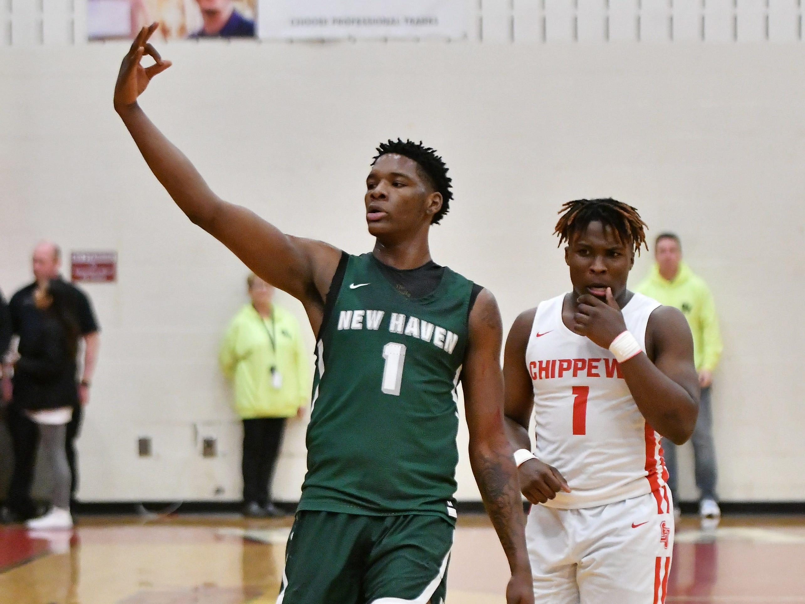 New Haven's Romeo Weems signals three points towards the Chippewa Valley student section after he hits a three-point shot in the first half.