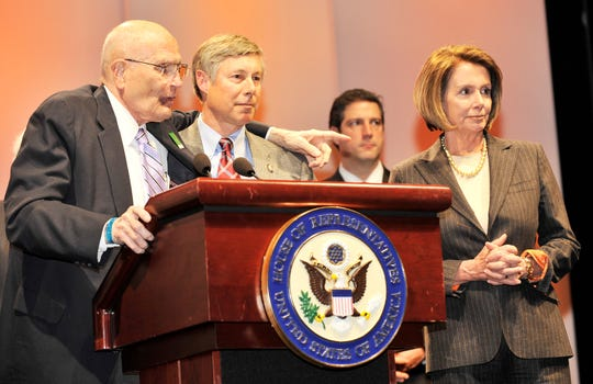 Rep. John Dingell puts his arm around Rep. Fred Upton during a Congressional delegation press conference at the Detroit auto show in 2010, with Speaker of the House Nancy Pelosi.